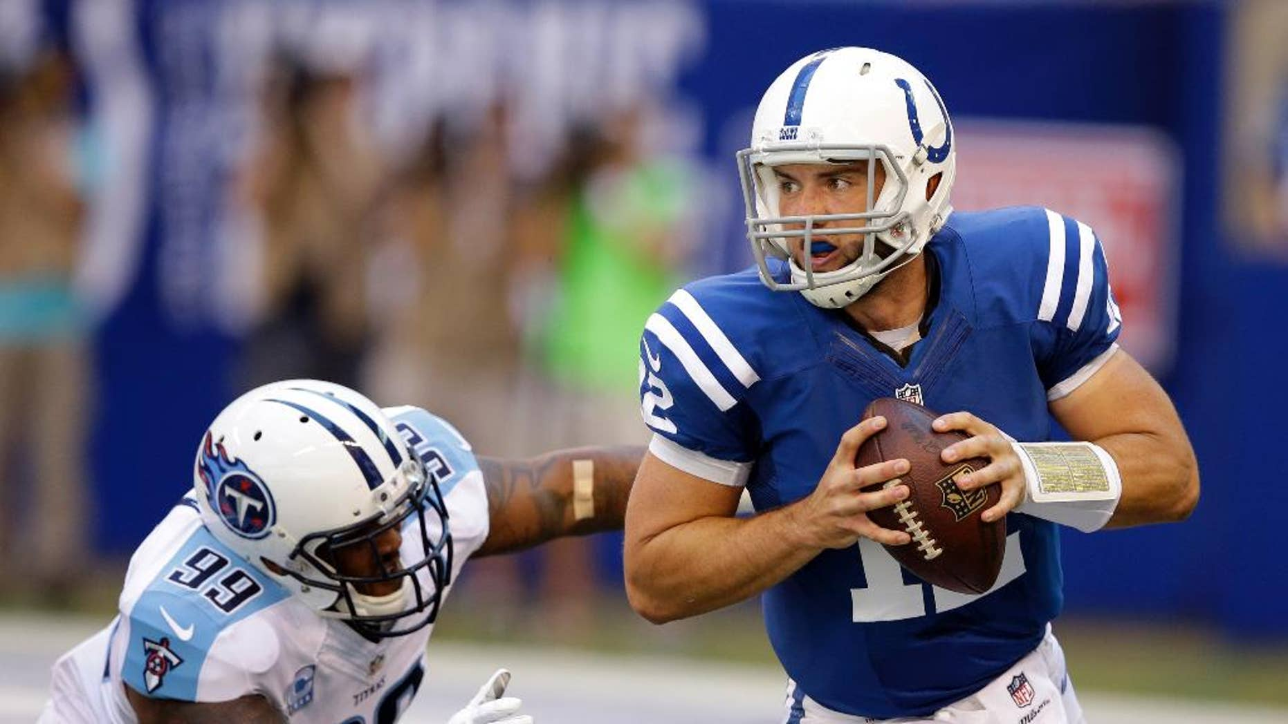 Tennessee Titans defensive end Jurrell Casey, left, chases Indianapolis Colts quarterback Andrew Luck during the first half of an NFL football game in Indianapolis, Sunday, Sept. 28, 2014. (AP Photo/Darron Cummings)