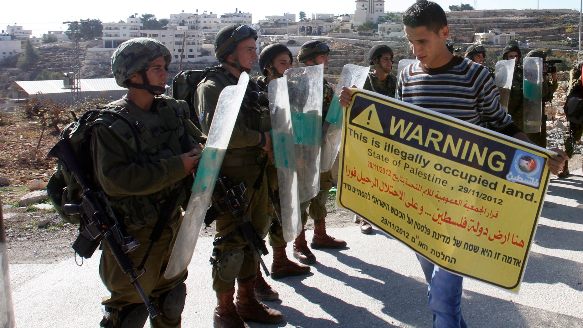 Nov. 30, 2012 -Palestinian protester holds placard in front of Israeli soldiers during a demonstration in the West Bank village of al-Masara near Bethlehem.