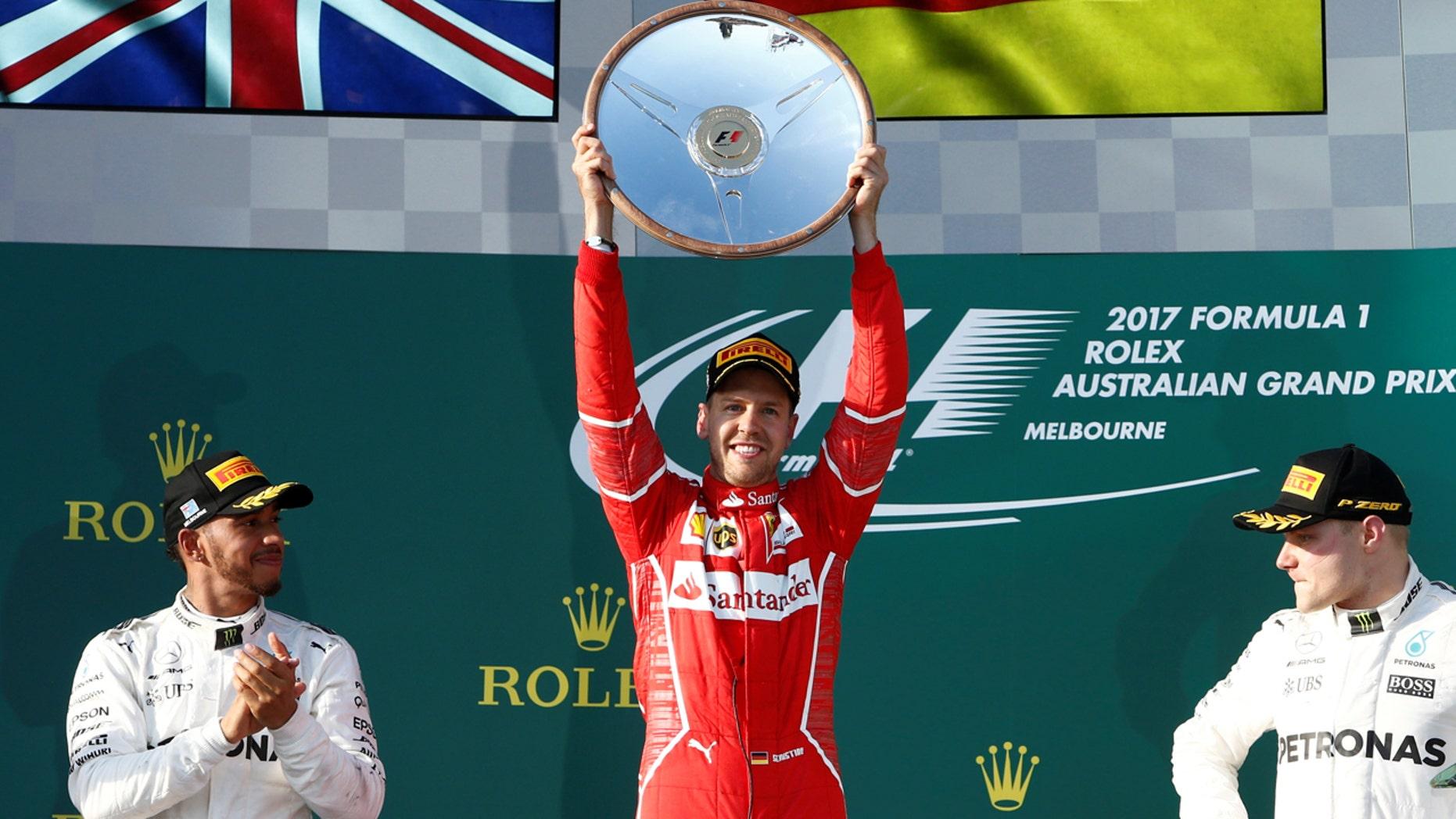 Formula One - F1 - Australian Grand Prix - Melbourne, Australia - 26/03/2017 - Ferrari driver Sebastian Vettel of Germany (C) celebrates alongside Mercedes driver Lewis Hamilton of Britain (L) and team mate Valtteri Bottas of Finland.    REUTERS/Brandon Malone     TPX IMAGES OF THE DAY - RTX32QM8