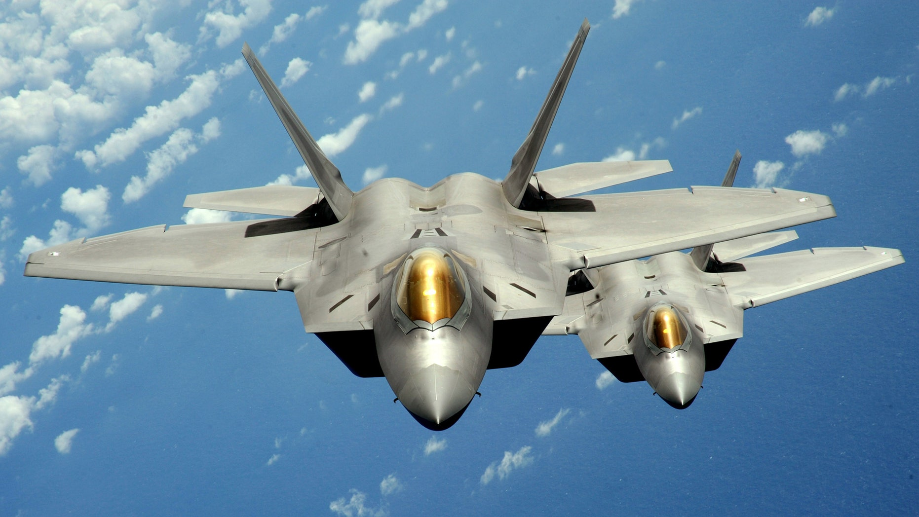 Two U.S. Air Force F-22 Raptor stealth jet fighters fly near Andersen Air Force Base in this handout photo dated August 4, 2010. (REUTERS/U.S. Air Force/Master Sgt. Kevin J. Gruenwald/Handout)