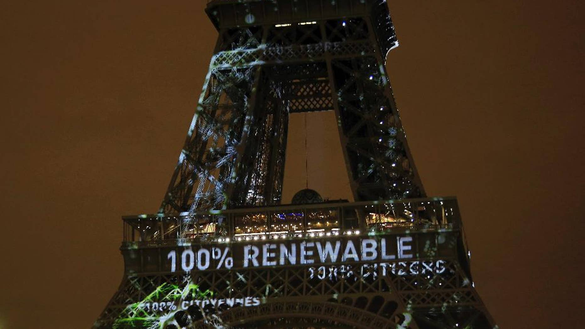 FILE- In this Sunday, Nov. 29, 2015 file photo, an artwork entitled 'One Heart One Tree' by artist Naziha Mestaoui is displayed on the Eiffel tower ahead of the 2015 Paris Climate Conference, in Paris. The Paris Agreement on climate change comes into force Friday Nov. 4, 2016, after a year with remarkable success in international efforts to slash man-made emissions of carbon dioxide and other global warming gases. (AP Photo/Thibault Camus, FILE)
