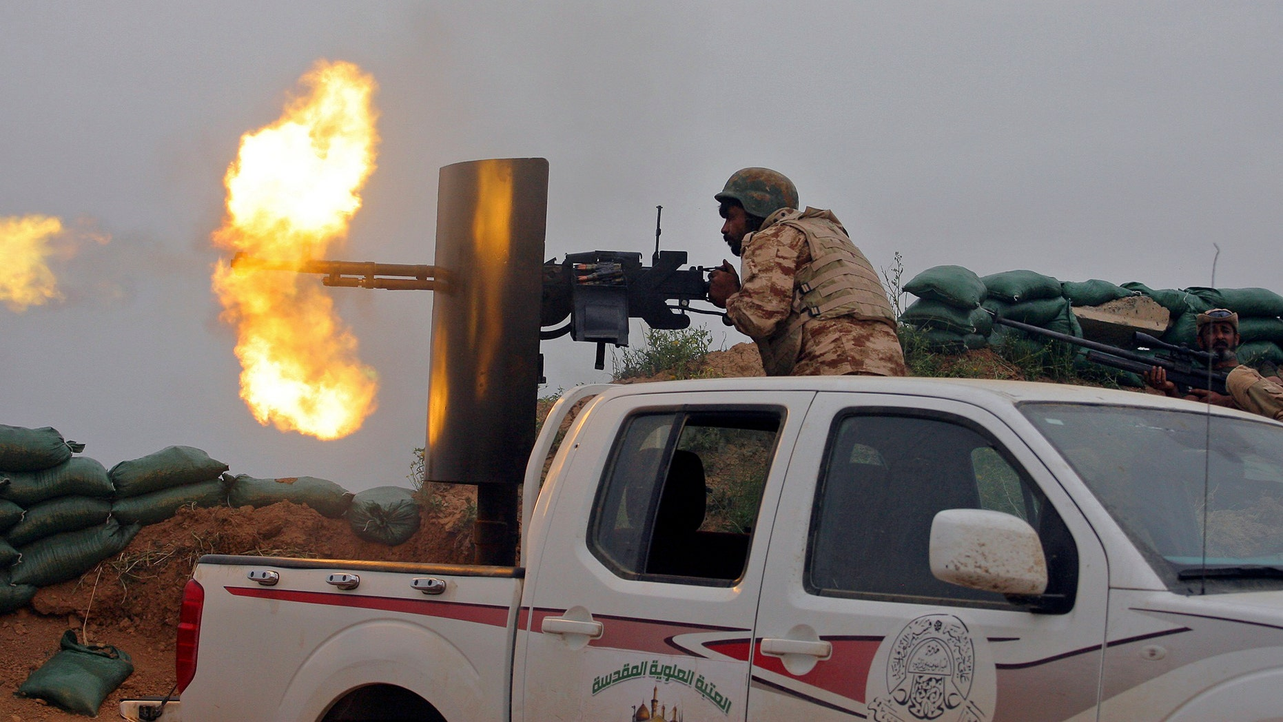 Iraqi Security forces and allied Popular Mobilization forces fire towards positions in the Islamic State group held town of Besher, during a military operation to regain control of the small town, outside the oil-rich city of Kirkuk, 180 miles (290 kilometers) north of Baghdad, Iraq, Sunday, April 10, 2016. (AP Photo/Anmar Khalil)