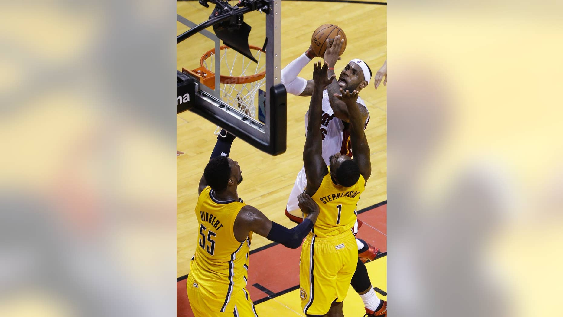 Miami Heat forward LeBron James (6) drives to the basket against Indiana Pacers guard Lance Stephenson (1) and center Roy Hibbert (55) during the first half of Game 3 in the NBA basketball Eastern Conference playoff series, Saturday, May 24, 2014, in Miami. (AP Photo/Wilfredo Lee)