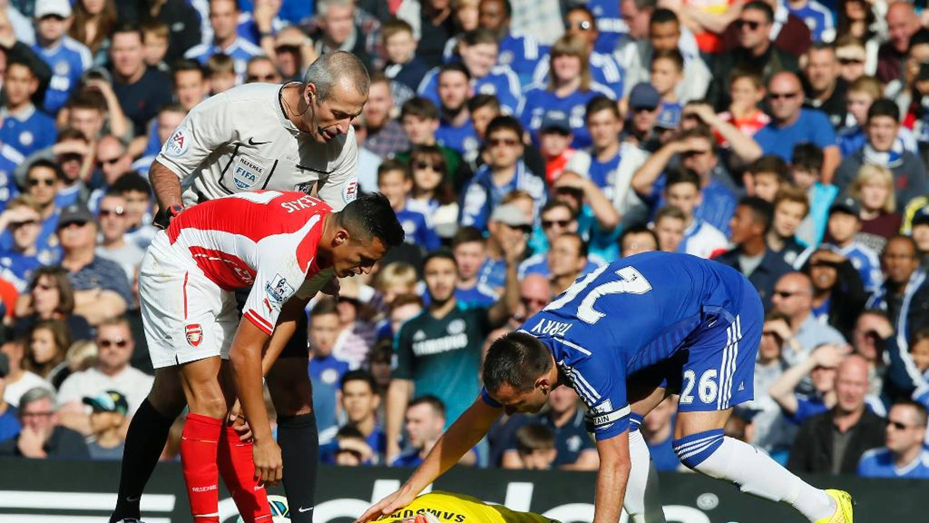 Arsenal's Alexis Sanchez, left, gets up after colliding with Chelsea's goalkeeper Thibaut Courtois, who lies on the ground attended to by teammate Chelsea's John Terry, right, during their English Premier League soccer match between Chelsea and Arsenal at Stamford Bridge stadium in London Sunday, Oct. 5, 2014. (AP Photo/Alastair Grant)