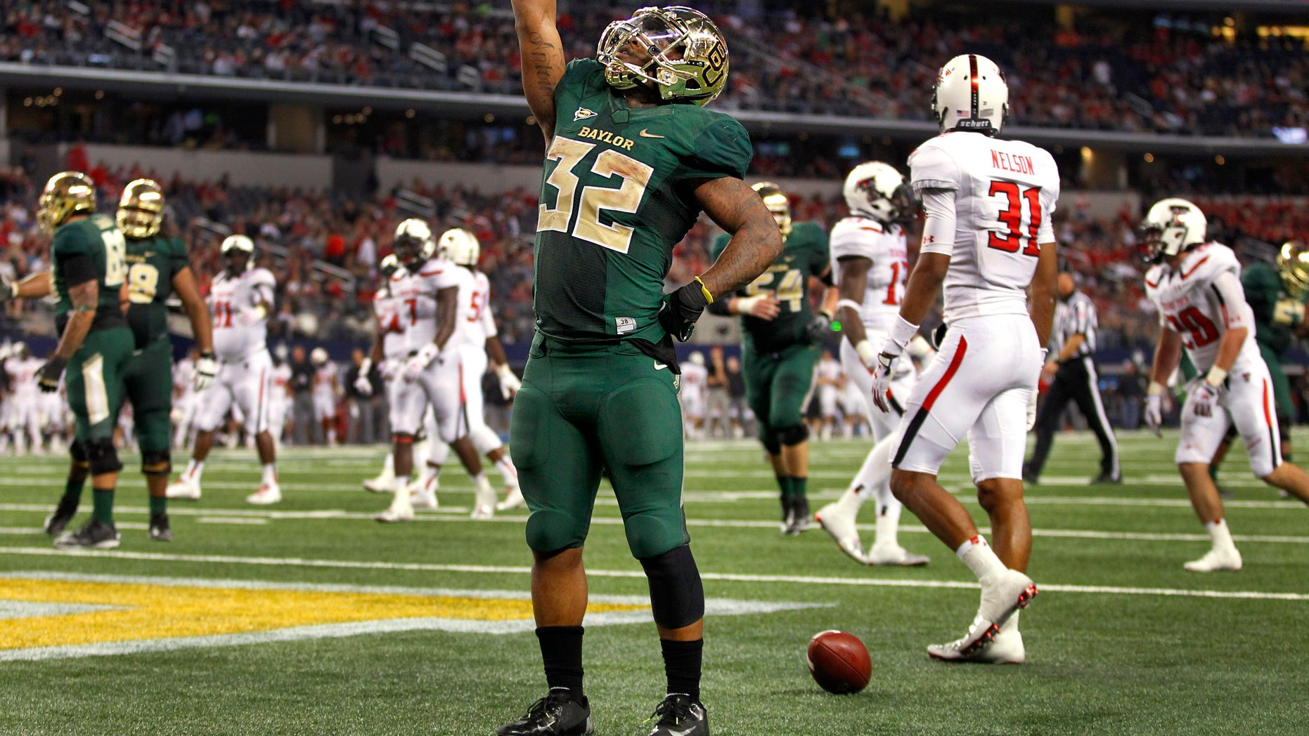 Baylor Bears running back Shock Linwood (32) points skyward after running in a fourth quarter touchdown against the Texas Tech Red Raiders defense at AT&T Stadium in Arlington, TX Saturday, Nov. 16, 2013. (AP Photo/Louis DeLuca/Dallas Morning News)