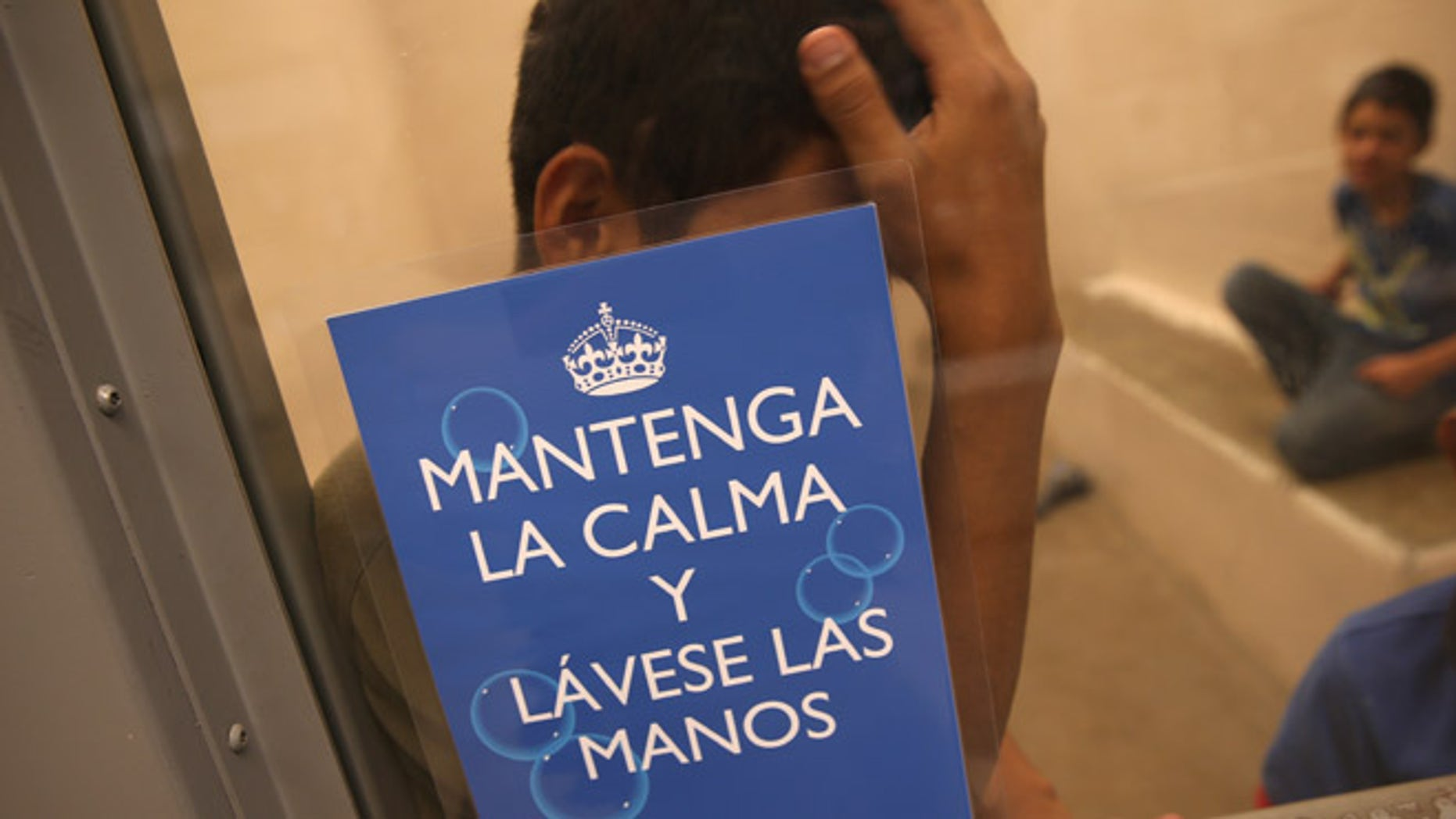 "MCALLEN, TX - SEPTEMBER 08:  Junvenile immigrants wait in a holding cell at a U.S. Border Patrol processing center for immigrants detained near the U.S.-Mexico border on September 8, 2014 in McAllen, Texas. The sign, written by the U.S. Centers for Disease Control (CDC), reads ""Maintain Calm and Wash Your Hands."" Thousands of immigrants, many of them families and unaccompanied minors, continue to cross illegally into the United States, although the numbers are down from a springtime high. Texas' Rio Grande Valley area is the busiest sector for illegal border crossings into the United States.  (Photo by John Moore/Getty Images)"