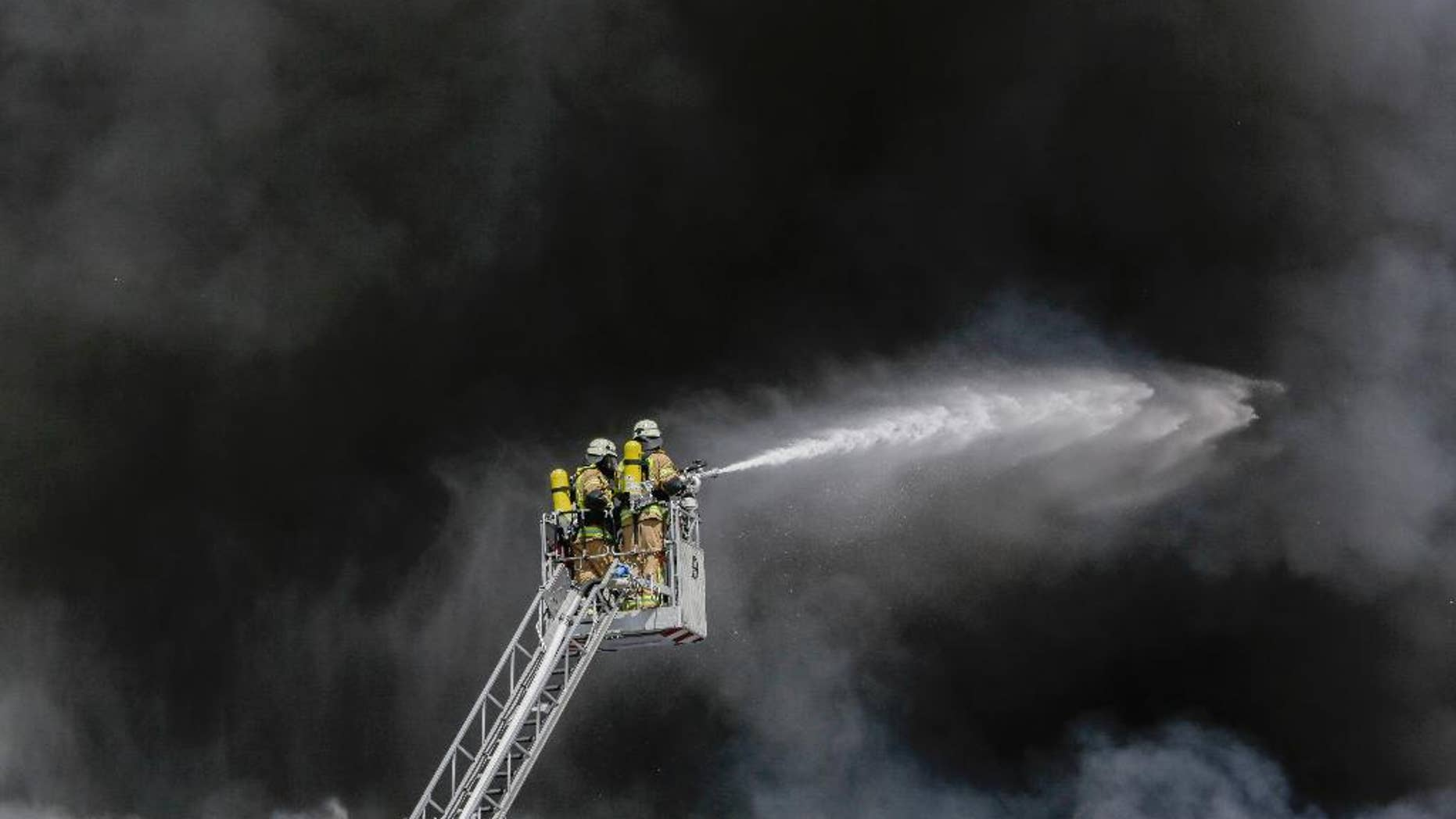 Fire fighters spray water in front of smoke at a burning storage hall of the Dong Xuan Center, an Asia market specialized in Vietnamese goods, in Berlin, Germany, Wednesday, May 11, 2016. The fire department sent some 150 trucks and other vehicles to the fire which broke out Wednesday morning . (AP Photo/Markus Schreiber)