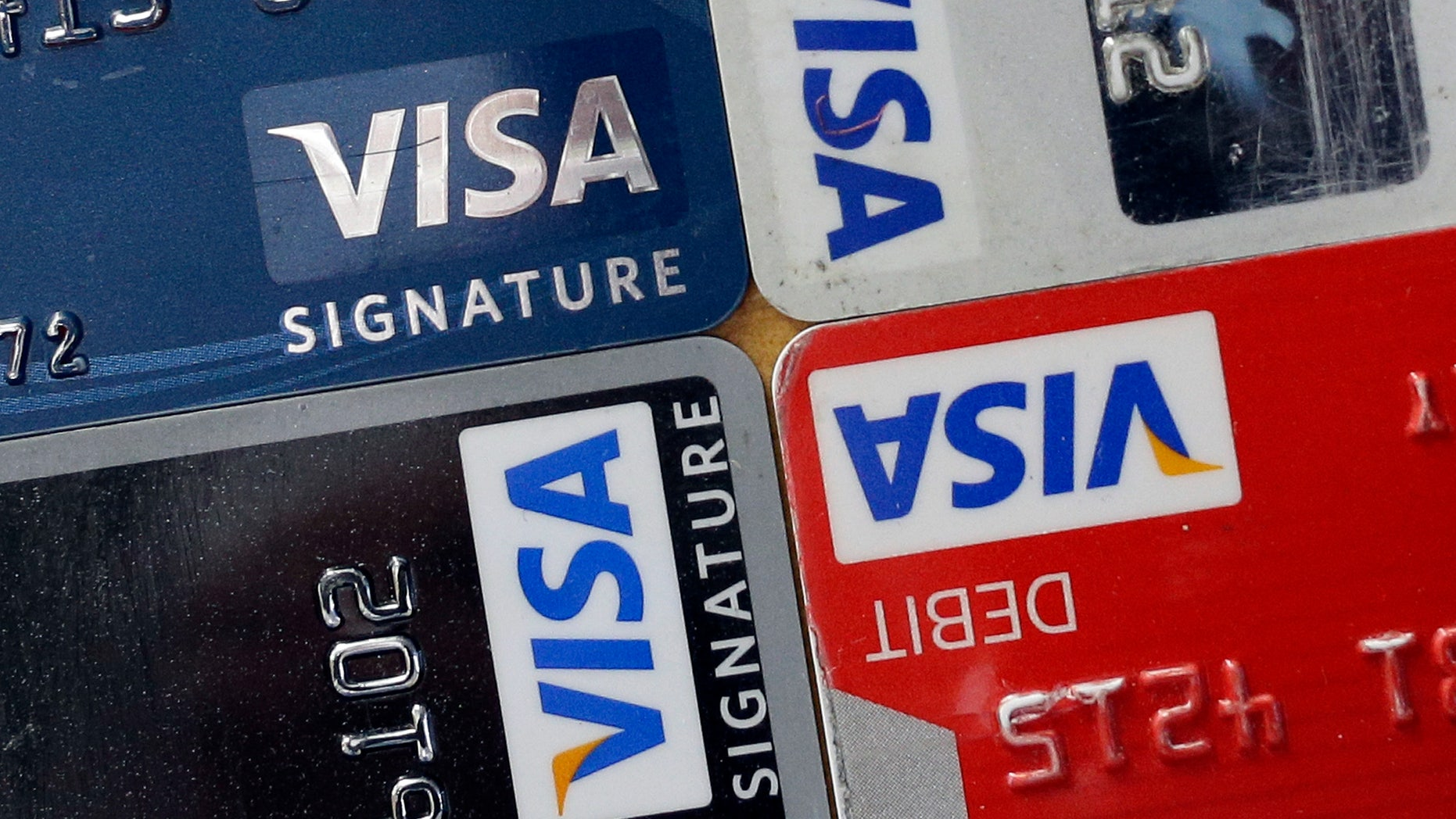 FILE - In this April 25, 2013 file photo, credit and debit cards are displayed for a photographer in Baltimore. Visa Inc. reports quarterly financial results after the market closes on Wednesday, Oct, 30, 2013. (AP Photo/Patrick Semansky, File)
