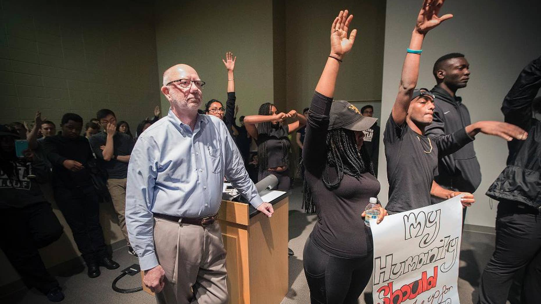 St. Olaf College President David R. Anderson is surrounded by student protesters in the Tomson Hall auditorium on campus in Northfield, Minn. May 1, 2017
