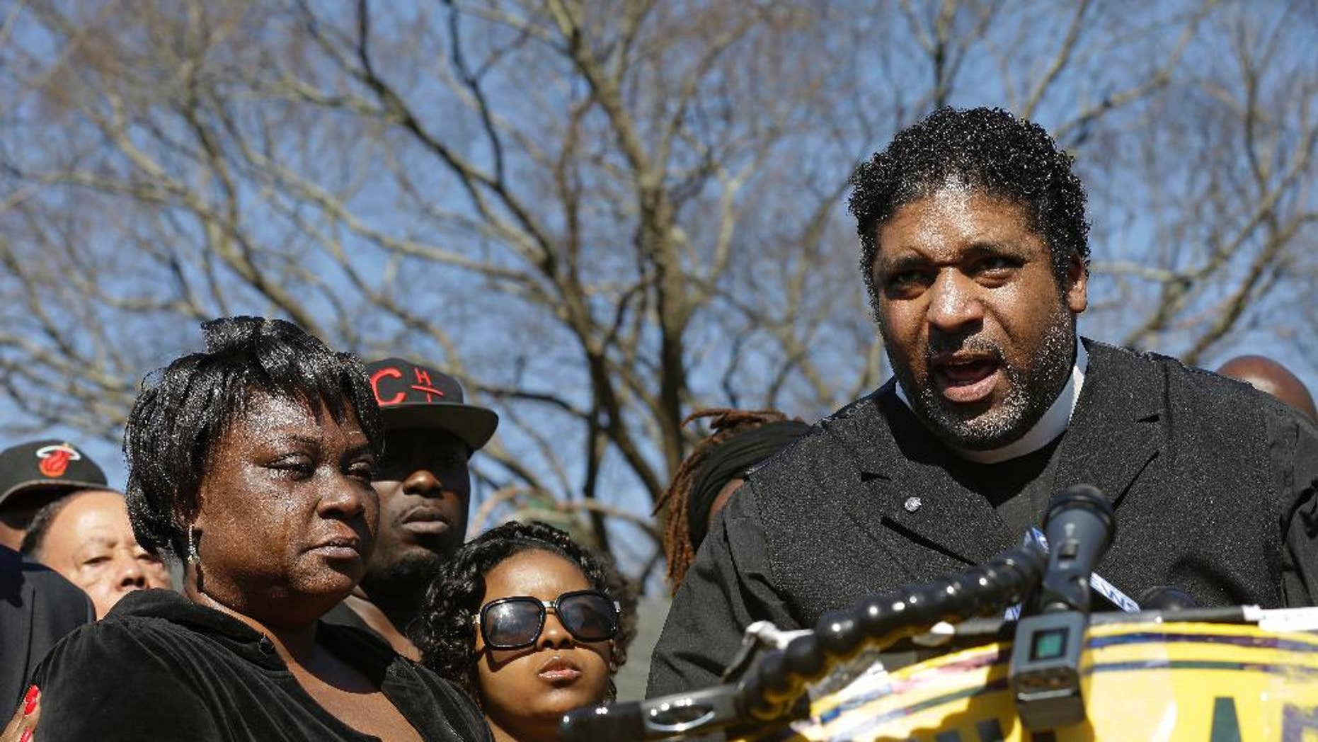 FILE - In this March 1, 2016, file photo, The Rev. William Barber II, right, head of the North Carolina National Association for the Advancement of Colored People, speaks during a news conference as Rolonda Byrd, left, who says she is the mother of shooting victim Akiel Denkins, listens near the scene of a shooting in Raleigh, N.C. Barber and the Rev. James Forbes said Monday, March 28, 2016, that they want to encourage people to reclaim political discourse so that it focuses on love, justice and mercy. (AP Photo/Gerry Broome)