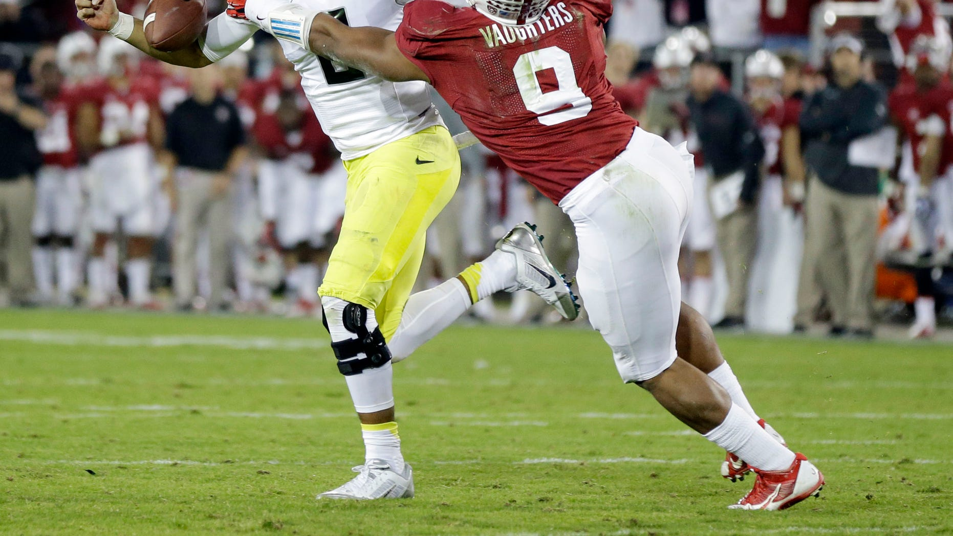 Oregon quarterback Marcus Mariota fumbles near the goal line while pressured by Stanford linebacker James Vaughters during the second half of an NCAA college football game on Thursday, Nov. 7, 2013, in Stanford, Calif. Oregon would recover the ball on the play. Stanford won 26-20. (AP Photo/Marcio Jose Sanchez)