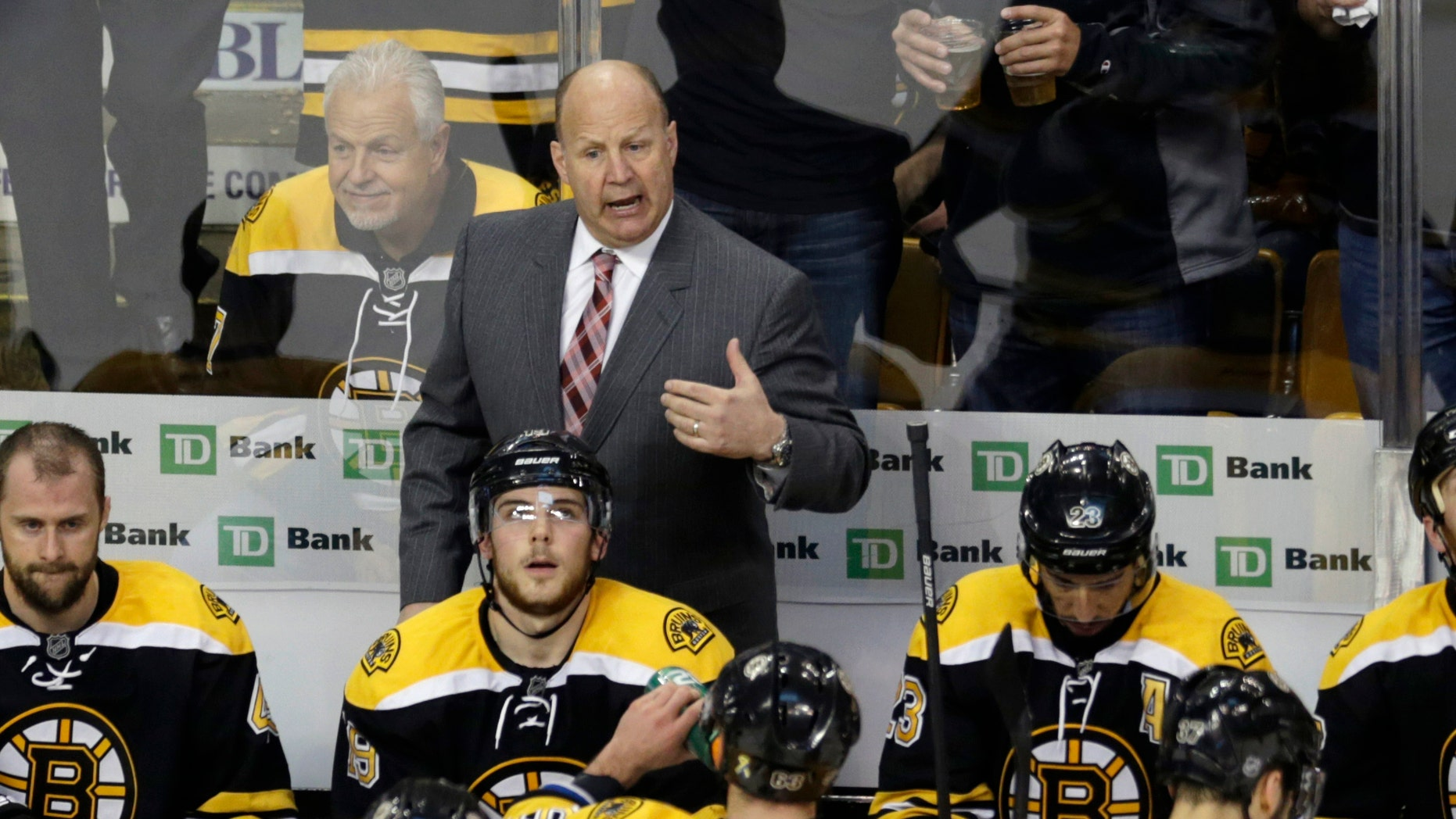 Boston Bruins head coach Claude Julien, standing center, talks with his players during a timeout against the New York Rangers during the third period in Game 5 of the Eastern Conference semifinals in the NHL hockey Stanley Cup playoffs in Boston, Saturday, May 25, 2013. (AP Photo/Charles Krupa)