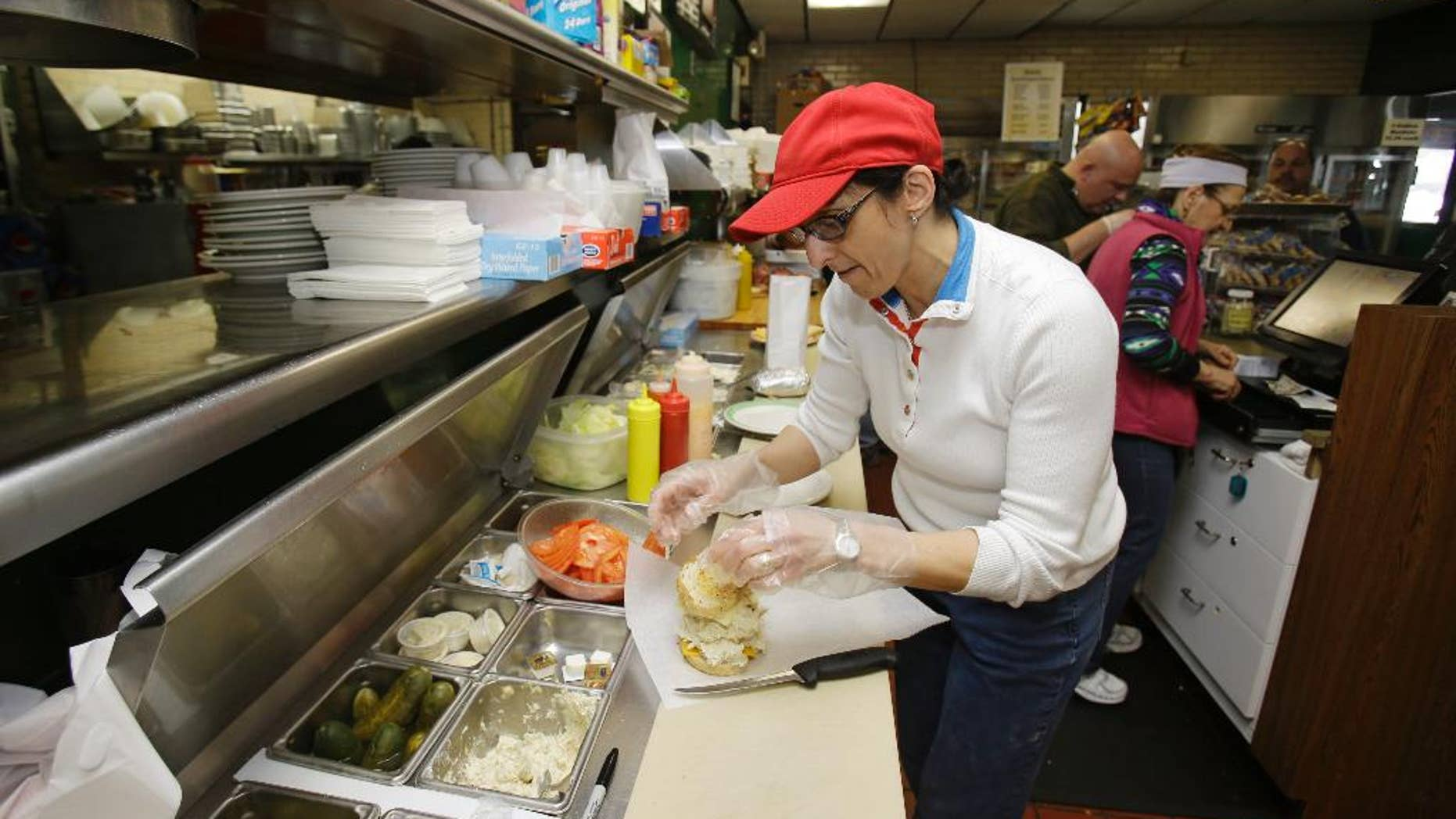 In this Friday, Jan. 23, 2015 photo, Collett Elkhouria makes a chicken salad sandwich the Superior Restaurant in Cleveland. The Institute for Supply Management releases its service sector index for February on Wednesday, March 4, 2015. (AP Photo/Tony Dejak)