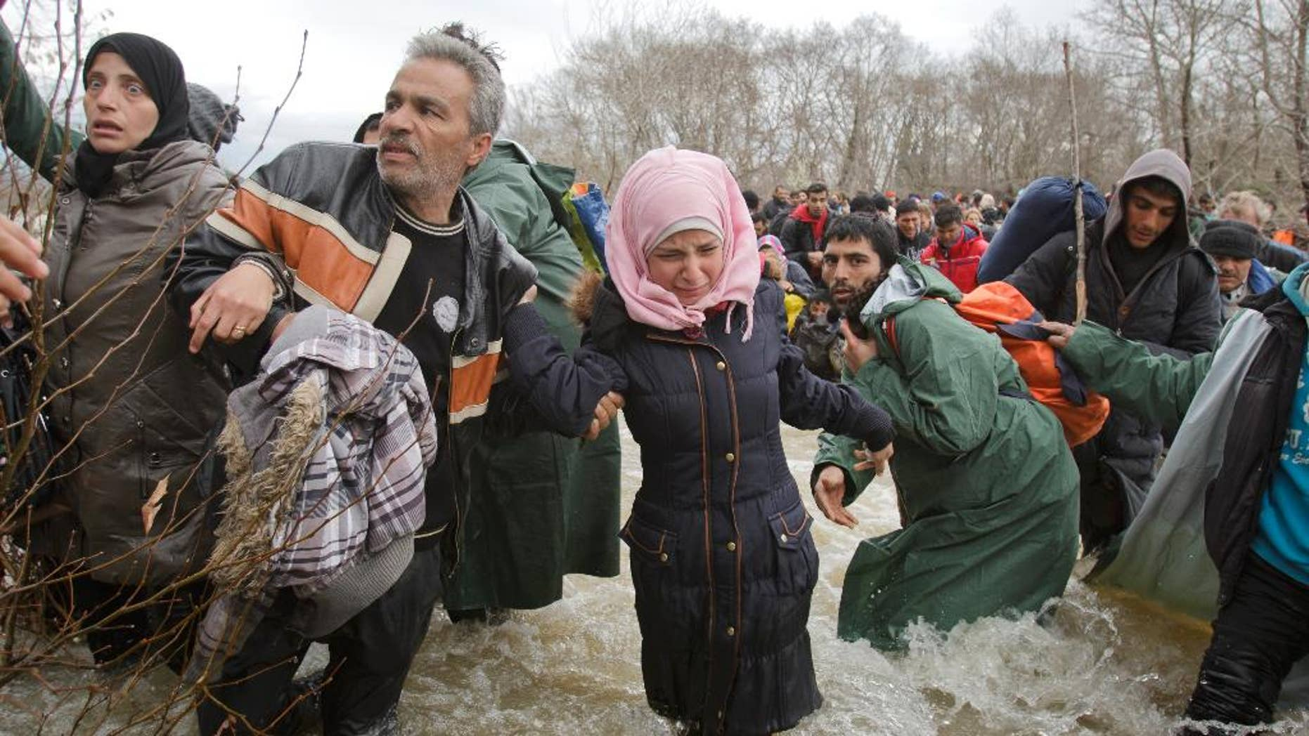FILE - In this Monday, March 14, 2016 file photo, a woman cries as she crosses the river along with other migrants attempting to reach Macedonia on a route that would bypass the border fence, north of Idomeni, Greece. Eight asylum seekers are taking legal action against Macedonia for expelling them back to Greece after a chaotic mass border crossing earlier this year. The migrant advocacy group ProAsyl said it helped the group file a complaint Monday, Sept. 12 with the Council of Europe's Court of Human Rights. (AP Photo/Vadim Ghirda, file)