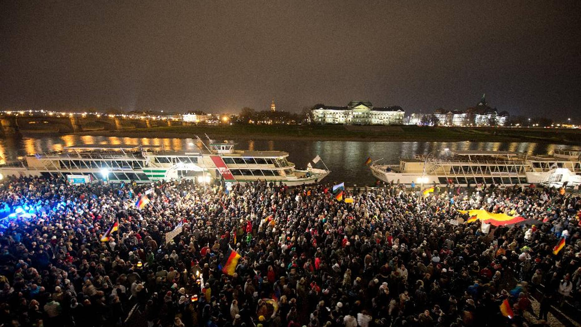 FILE - In this Dec. 1, 2014 file picture participants of a right-wing group's march  called  'Patriotic Europeans against the Islamization of the  West'  (PEGIDA,)  gather  in Dresden, Germany.  The eastern German city of Dresden is bracing itself for one of the biggest far-right marches the country has seen in years. City officials say Friday Dec. 5, 2014 organizers have told them 8,000 will take part in the protest Monday, billed as a march against Islamic extremism. The protest is organized by a group called PEGIDA, a German acronym for 'Patriotic Europeans against the Islamization of the West.'  Over the past two months it has organized seven protests in Dresden, growing from 200 at the first march to 7,500 people last Monday. (AP Photo/dpa,Arno Burgi,File)