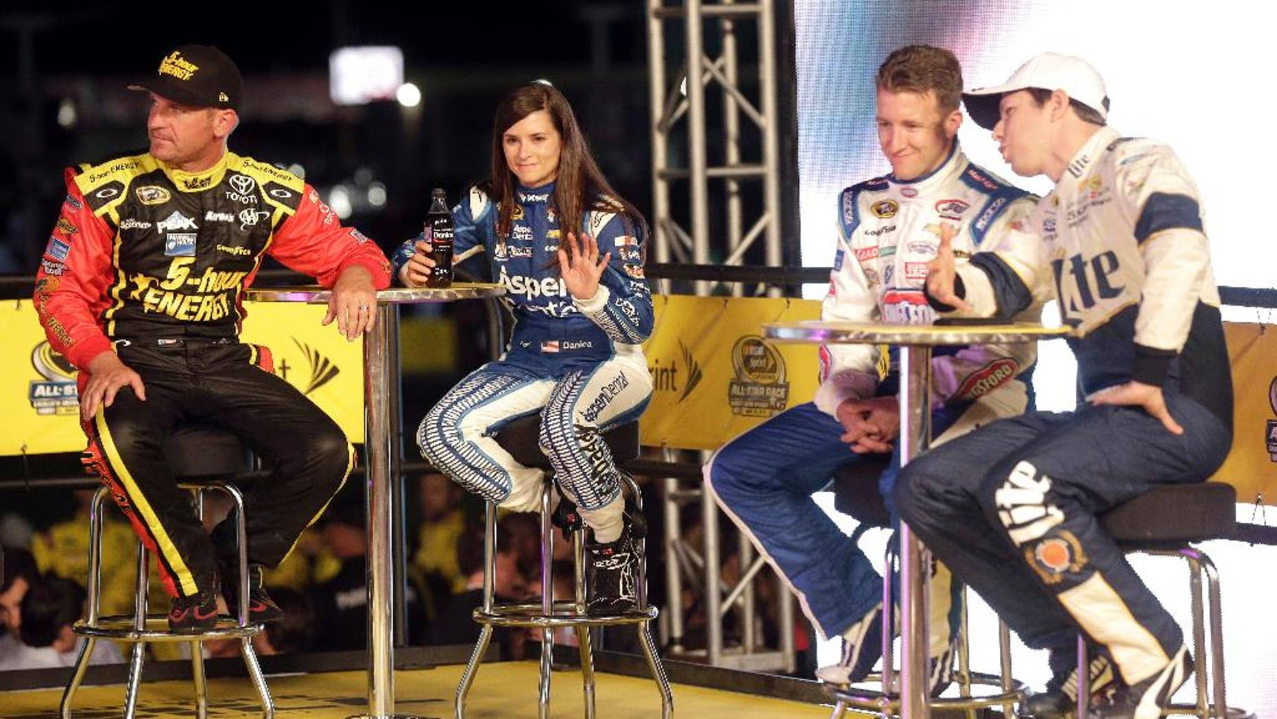 Clint Bowyer, Danica Patrick, AJ Allmendinger and Brad Keselowski, from right, watch during driver introductions prior to the NASCAR Sprint All-Star auto race at Charlotte Motor Speedway in Concord, N.C., Saturday, May 16, 2015. (AP Photo/Gerry Broome)