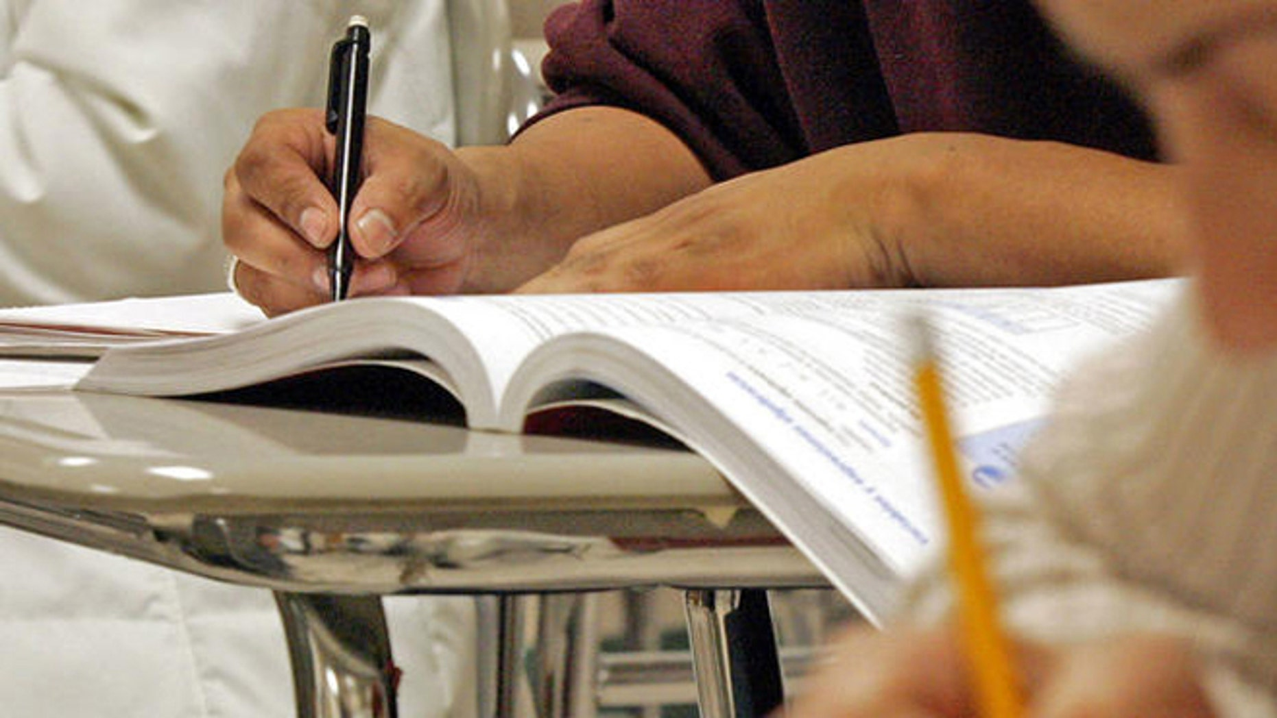 Students work out math problems during a class for Hispanic adults. (AP Photo/ Karl DeBlaker)