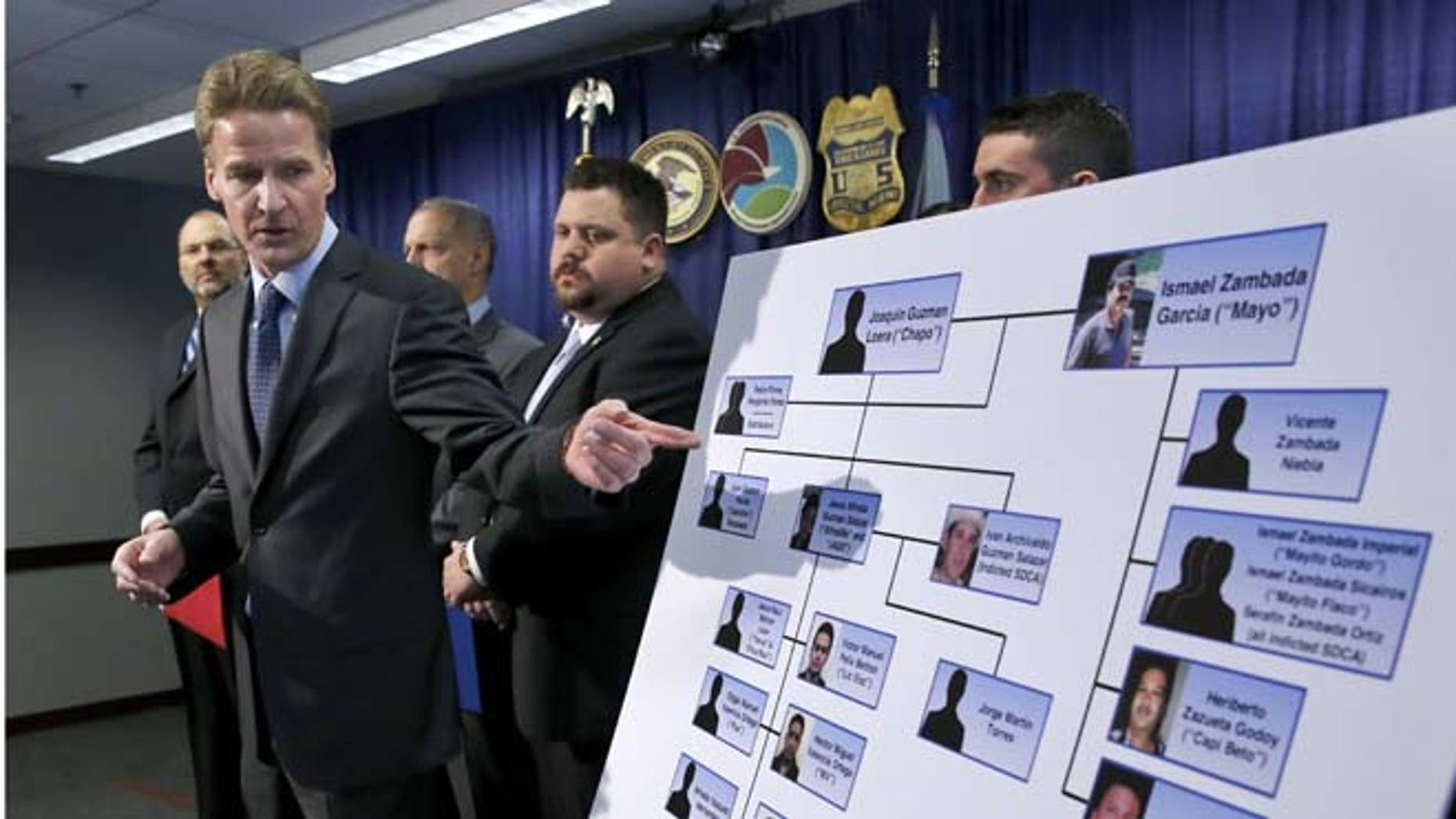 """U.S. Attorney Zachary T. Fardon makes reference to a chart of know Mexico-based Sinaloa Cartel members, during a news conference after twin brothers Pedro and Margarito Flores were sentenced to 14 years for their drug related activities in the cartel, Tuesday, Jan. 27, 2015, in Chicago. Fardon characterized the Flores brothers cooperation in bringing down the cartel as extraordinary. He says their reduced sentences should illustrate to criminals that, """"You can right some of what you did wrong, by helping the government."""" (AP Photo/Charles Rex Arbogast)"""