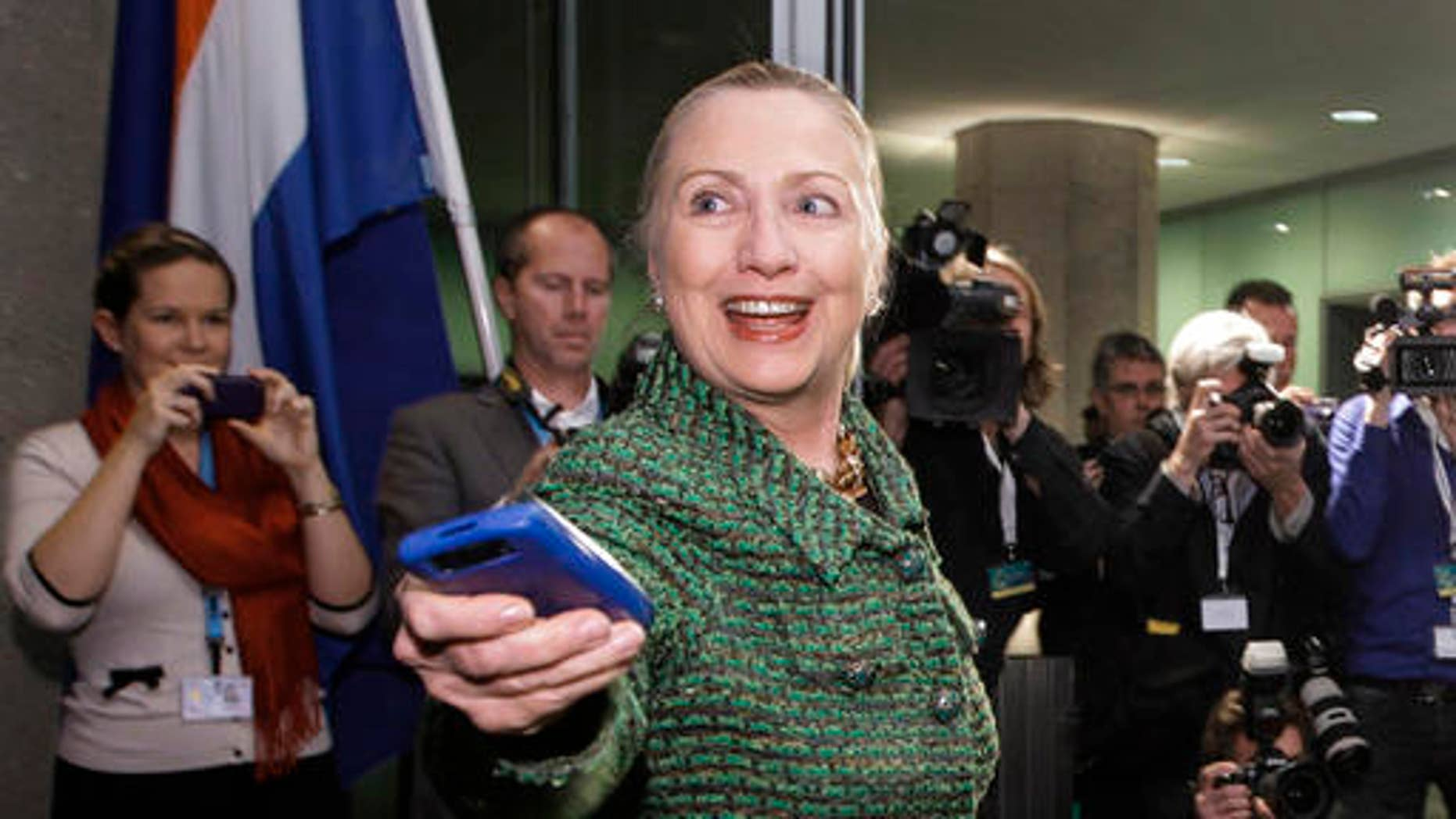FILE - Dec. 8, 2011: Then-Secretary of State Hillary Rodham Clinton hands off her mobile phone after arriving for a meeting in The Hague, Netherlands.