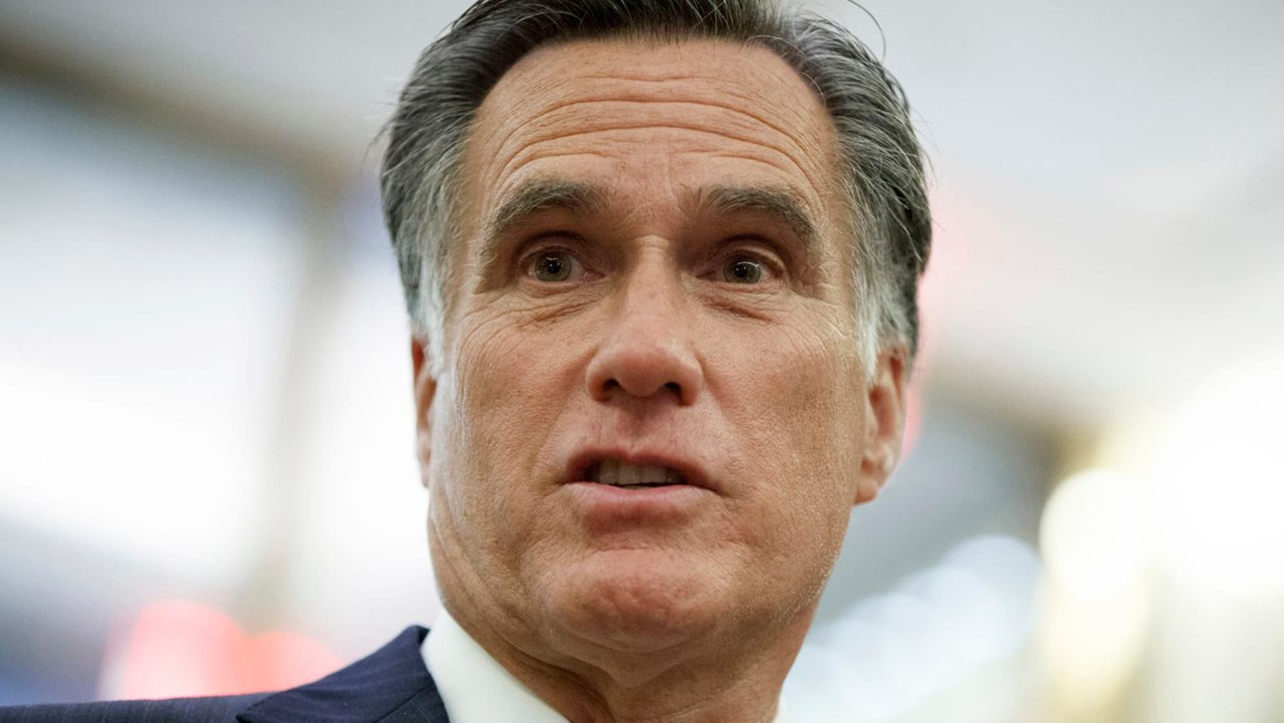 FILE - In this Tuesday, Nov. 29, 2016 file photo, former Republican presidential nominee Mitt Romney talks with reporters in New York.  Former Democratic Vice President Joe Biden is encouraging former Republican presidential candidate Mitt Romney to run for a senate seat in Utah currently held by Orrin Hatch if the senator decides to retire next year. Biden made the comment to Romney Friday, June 9, 2017 at a luxury resort in Utah, where Romney was hosting an annual invitation-only business and politics summit.. (AP Photo/Evan Vucci, File)