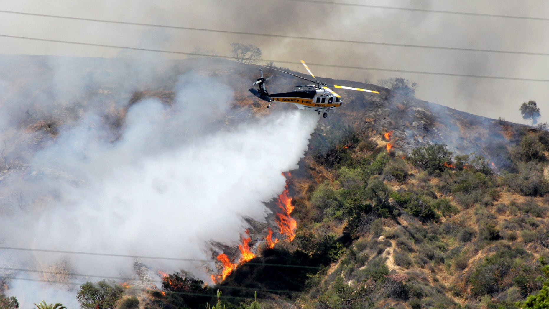 FILE - This Saturday April 20,2013 file photo shows a Los Angeles County Fire Department helicopter droping water on a fire burning on the foothills of the San Gabriel Mountains in Monrovia, Calif. Authorities say California is facing a dangerous wildfire season due to a dry winter that has left the normally green hills of spring parched and tinder-dry. (AP Photo/John Antczak,File)