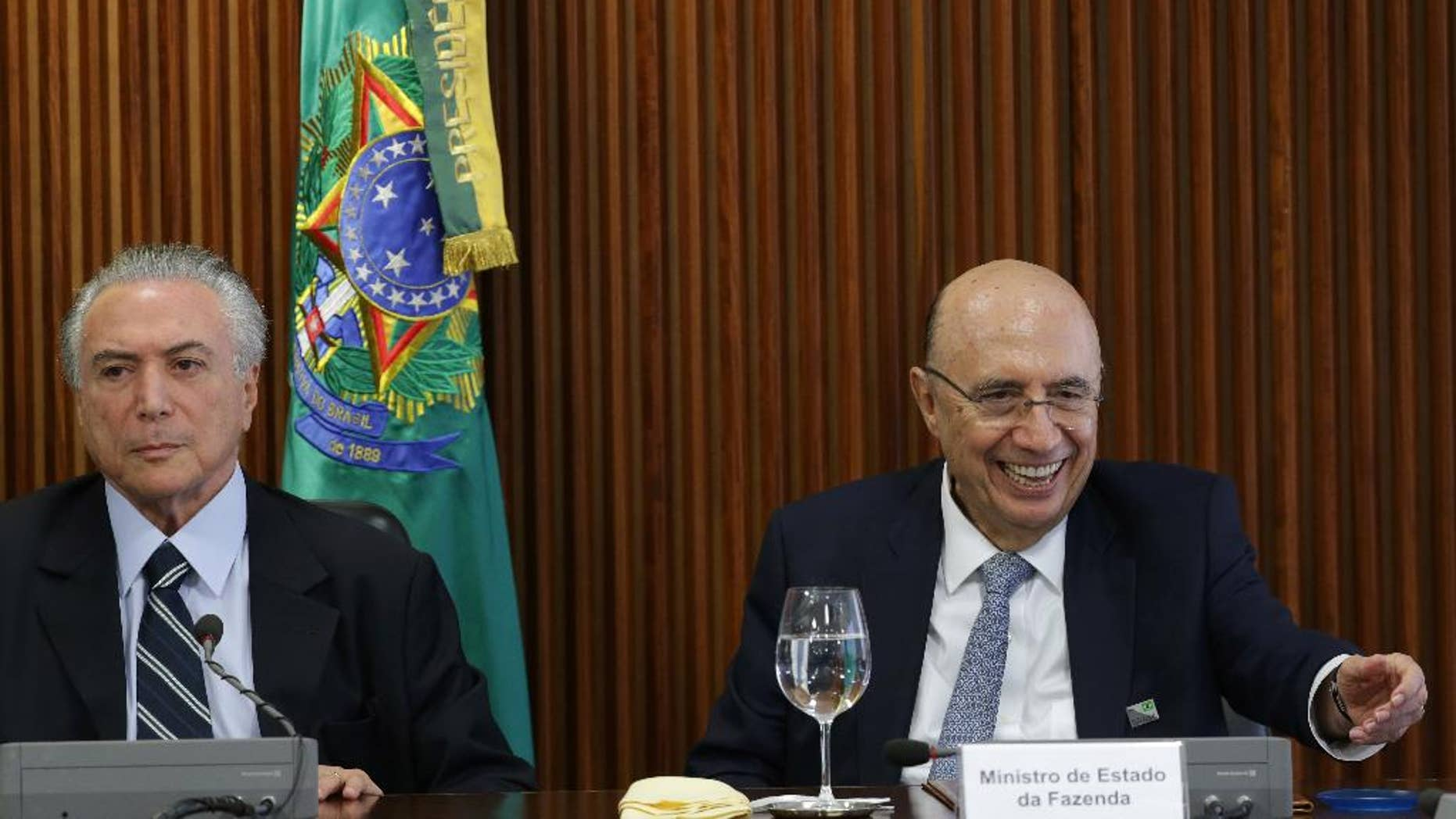 Brazil's acting President Michel Temer, left, presides over his first cabinet meeting, at the Planalto presidential palace in Brasilia, Brazil, Friday, May 13, 2016.  Newly named Finance Minister Henrique Meirelles is pictured at right. (AP Photo/Eraldo Peres)