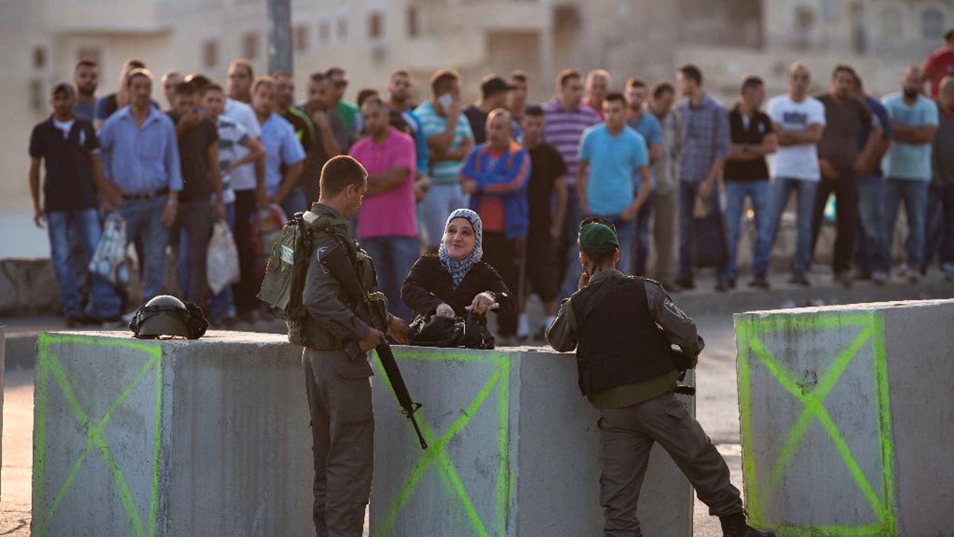 Israeli border police check Palestinian's IDs at a checkpoint as they exit the Arab neighborhood of Issawiyeh in Jerusalem, Sunday, Oct. 18, 2015. Palestinian assailants carried out a series of five stabbing attacks in Jerusalem and the West Bank on Saturday, as a month-long outburst of violence showed no signs of abating. The unrest came despite new security measures that have placed troops and checkpoints around Palestinian neighborhoods in east Jerusalem. (AP Photo/Oded Balilty)