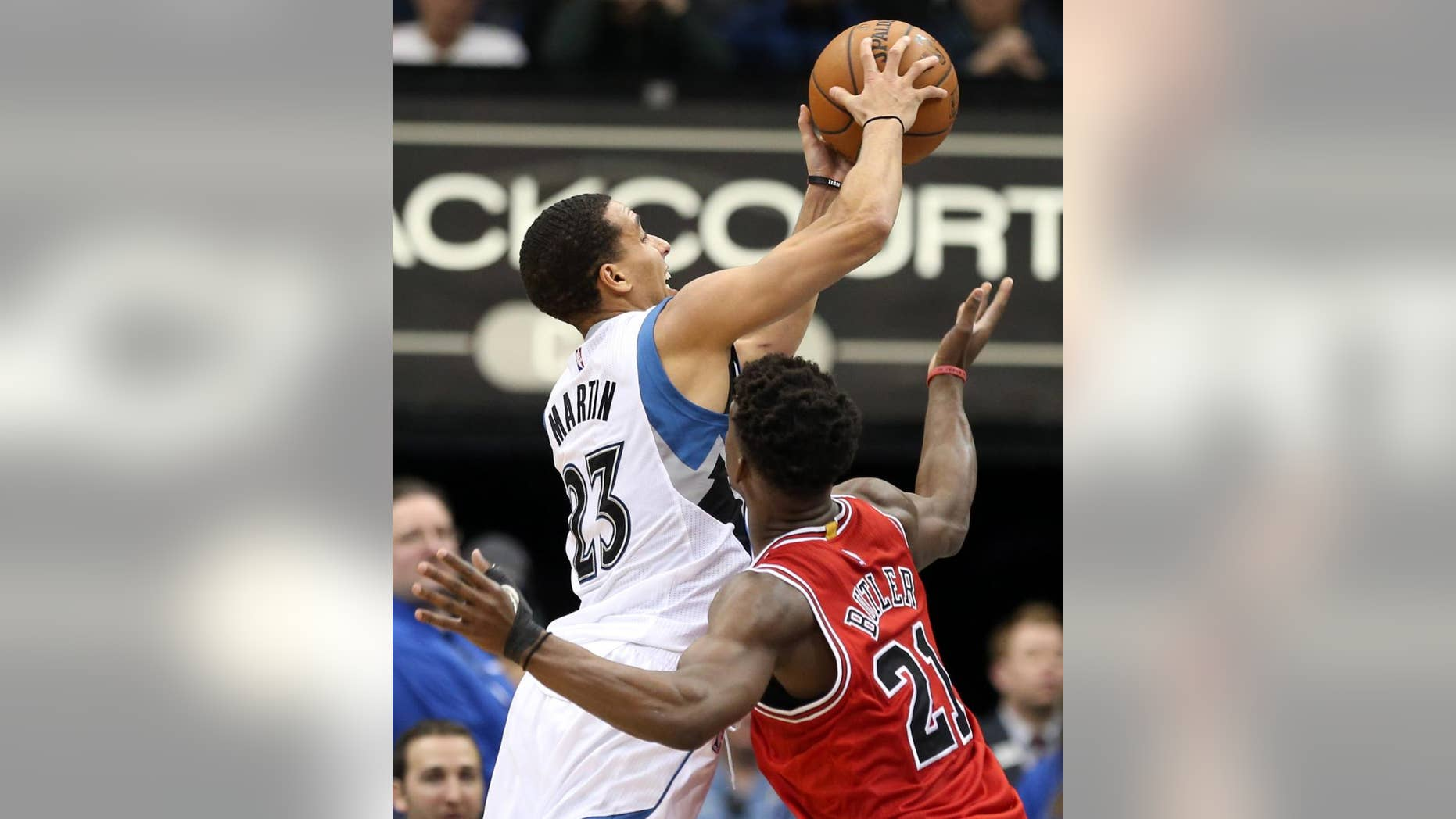 Minnesota Timberwolves' Kevin Martin , left, attempts a shot in front of Chicago Bulls' Jimmy Butler in the second half of an NBA basketball game, Saturday, Nov. 1, 2014, in Minneapolis. The Bulls won 106-105. MArtin led the Timberwolves with 33 points and Butler led the Bulls with 24.  (AP Photo/Jim Mone)
