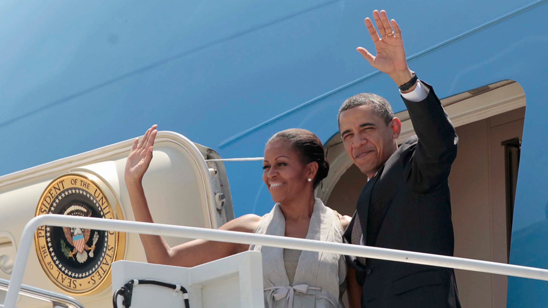 President Barack Obama and first lady Michelle Obama wave prior to boarding Air Force prior to departing San Salvador, El Salvador, Wednesday, March 23, 2011. (AP Photo/Pablo Martinez Monsivais)