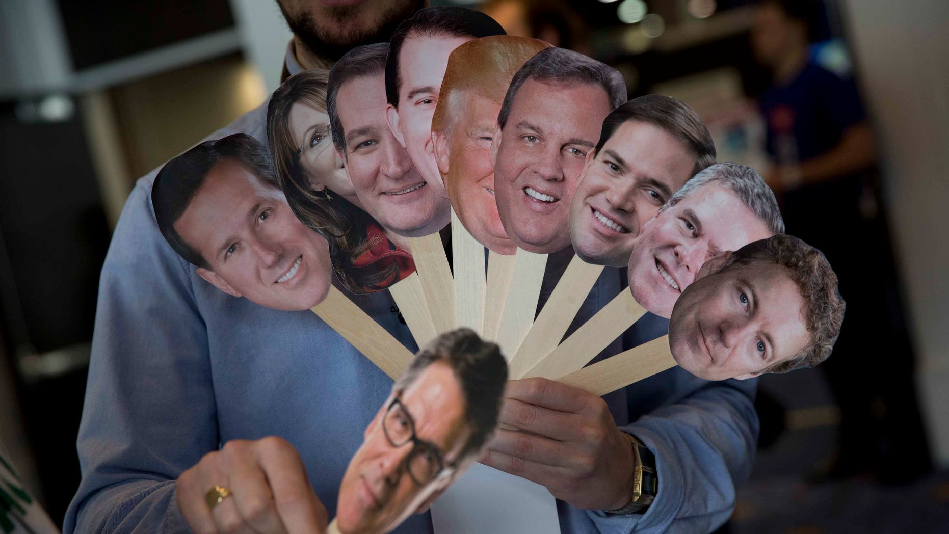 "Adam Gabbatt of The Guardian newspaper holds images of possible Republican candidates, from left, former Pennsylvania Sen. Rick Santorum, former Alaska Gov. Sarah Palin, Sen. Ted Cruz, R-Texas, Wisconsin Gov. Scott Walker, Donald Trump, New Jersey Gov. Chris Christie, Sen. Marco Rubio, R-Fla., former Florida Gov. Jeb Bush, Sen. Rand Paul, R-Ky., and, former Texas Gov. Rick Perry, bellow, as he interviews Howard ""Cowboy"" Woodward during the Conservative Political Action Conference (CPAC) in National Harbor, Md., Thursday, Feb. 26, 2015. (AP Photo/Carolyn Kaster)"
