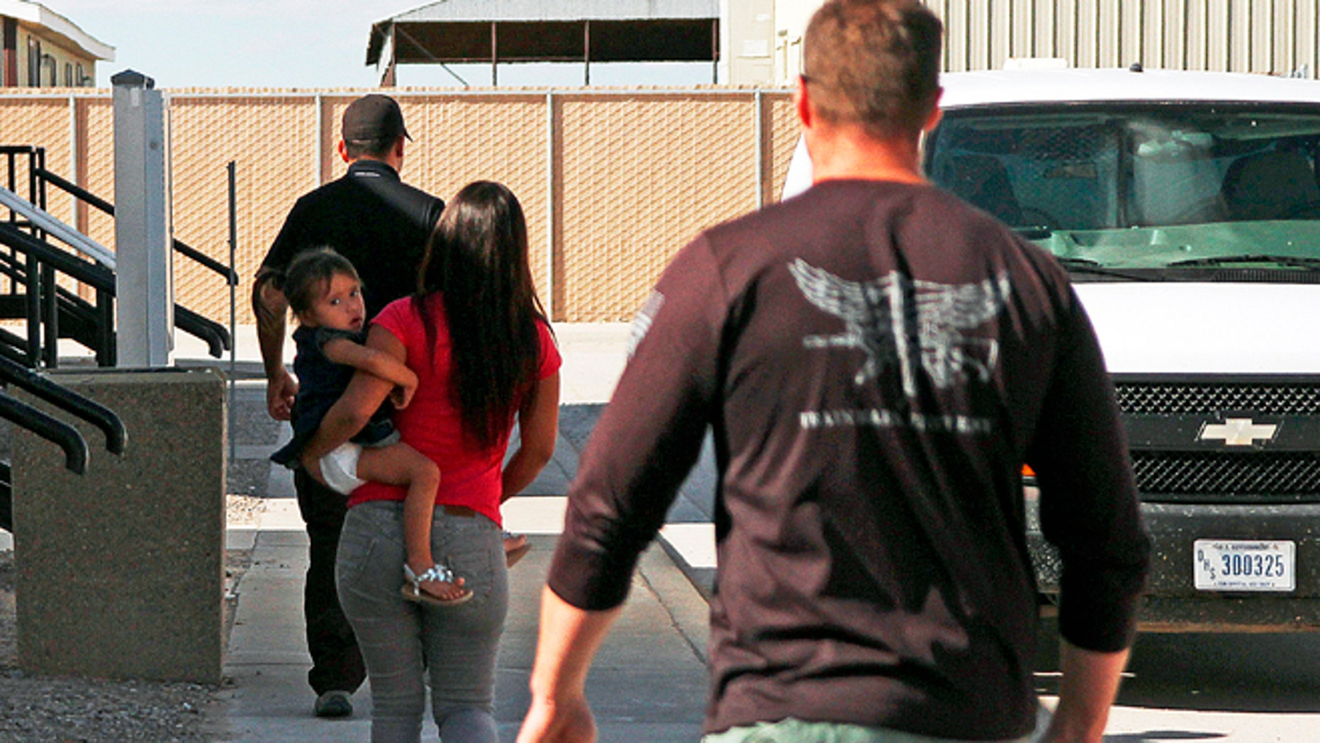 A woman and child are escorted to a van by detention facility guards inside the Artesia Family Residential Center, a federal detention facility for illegal immigrants and children in Artesia, N.M. (AP Photo/Juan Carlos Llorca, File)