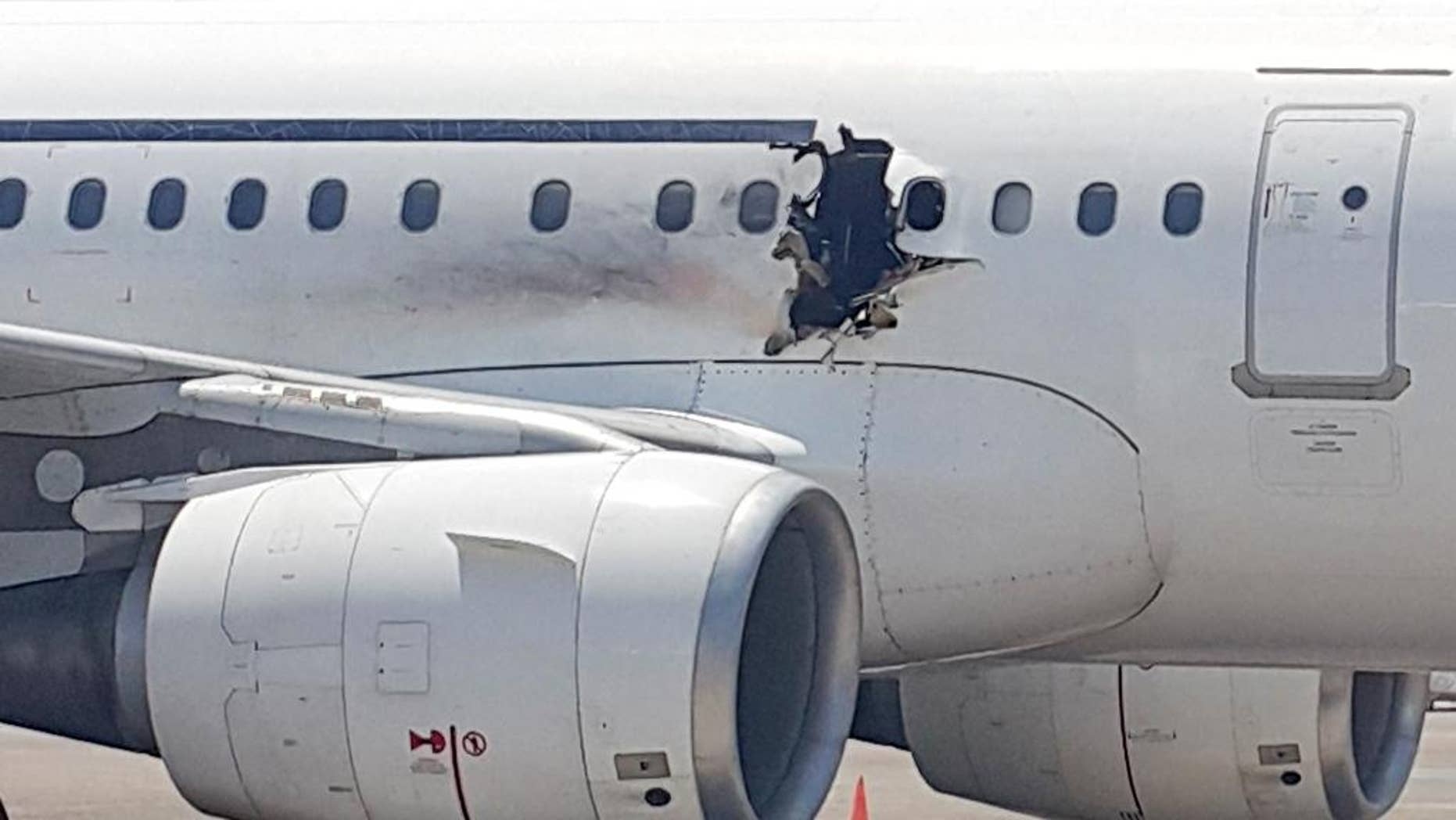 FILE - In this Tuesday, Feb. 2, 2016 file photo, of a  hole in a plane operated by Daallo Airlines as it sits on the runway of the airport in Mogadishu, Somalia. A military court in the Somali capital has given life terms Monday, May 30, 2016 to two men convicted of masterminding the bombing in February of the airliner which made an emergency landing with a gaping hole in its fuselage. (AP Photo, File)