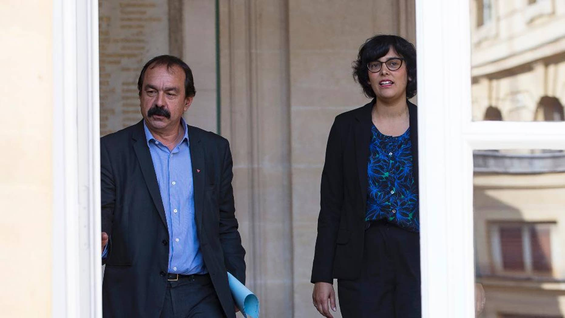 The leader of France's left-wing CGT union Philippe Martinez, left, and French Labor Minister Myriam El Khomri, leave the ministry after their meeting in Paris, Friday, June 17, 2016. Martinez, the main force of opposition to an unpopular labor reform bill that has led to violence in the streets, says he's asked the labor minister to suspend parliamentary debate on the measure and re-write it. (AP Photo)