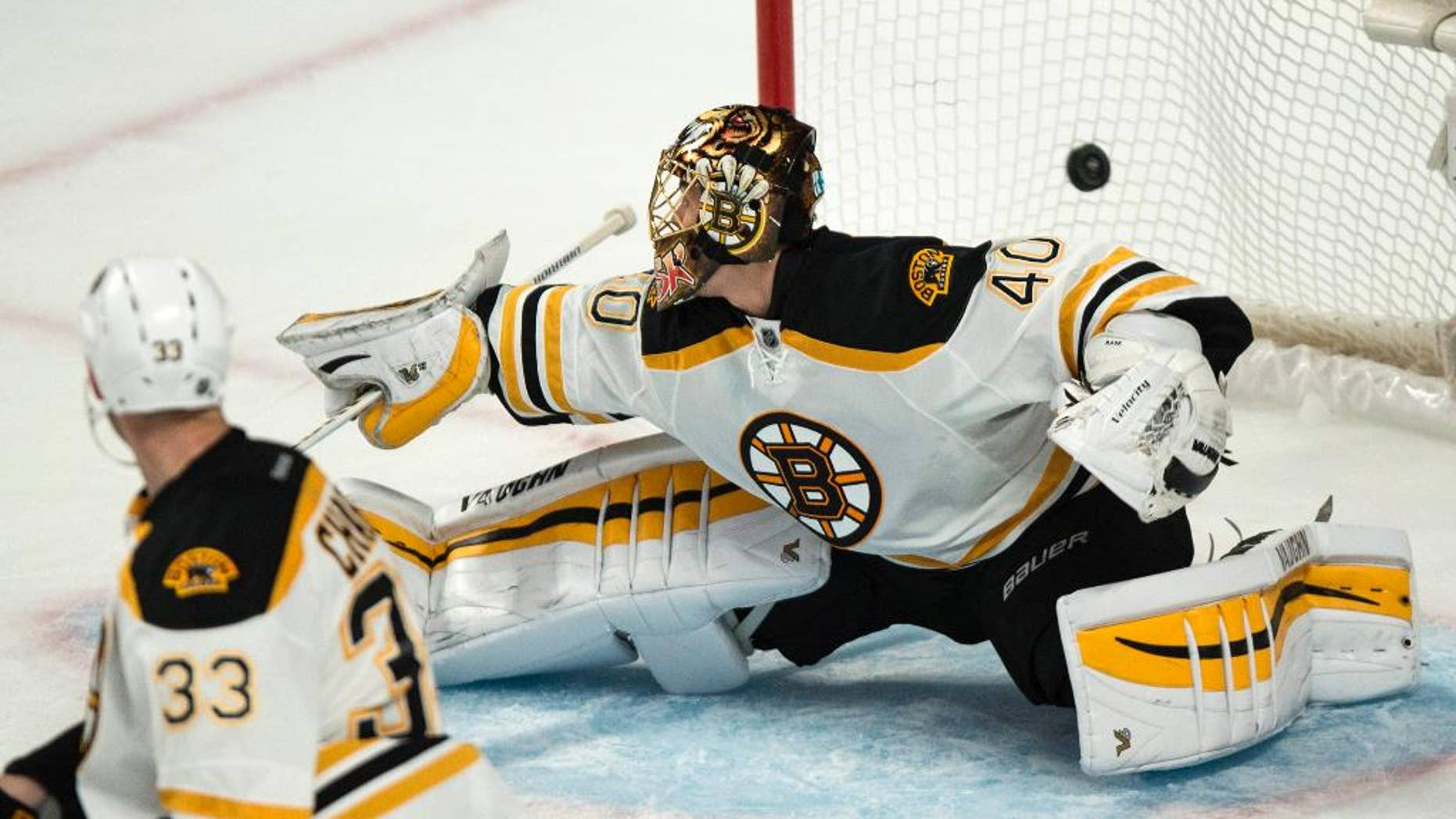 The puck flies over Boston Bruins goalie Tuukka Rask on a goal by Montreal Canadiens' P.A. Parenteau during second-period NHL hockey game action Thursday, Oct. 16, 2014, in Montreal. (AP Photo/The Canadian Press, Paul Chiasson)