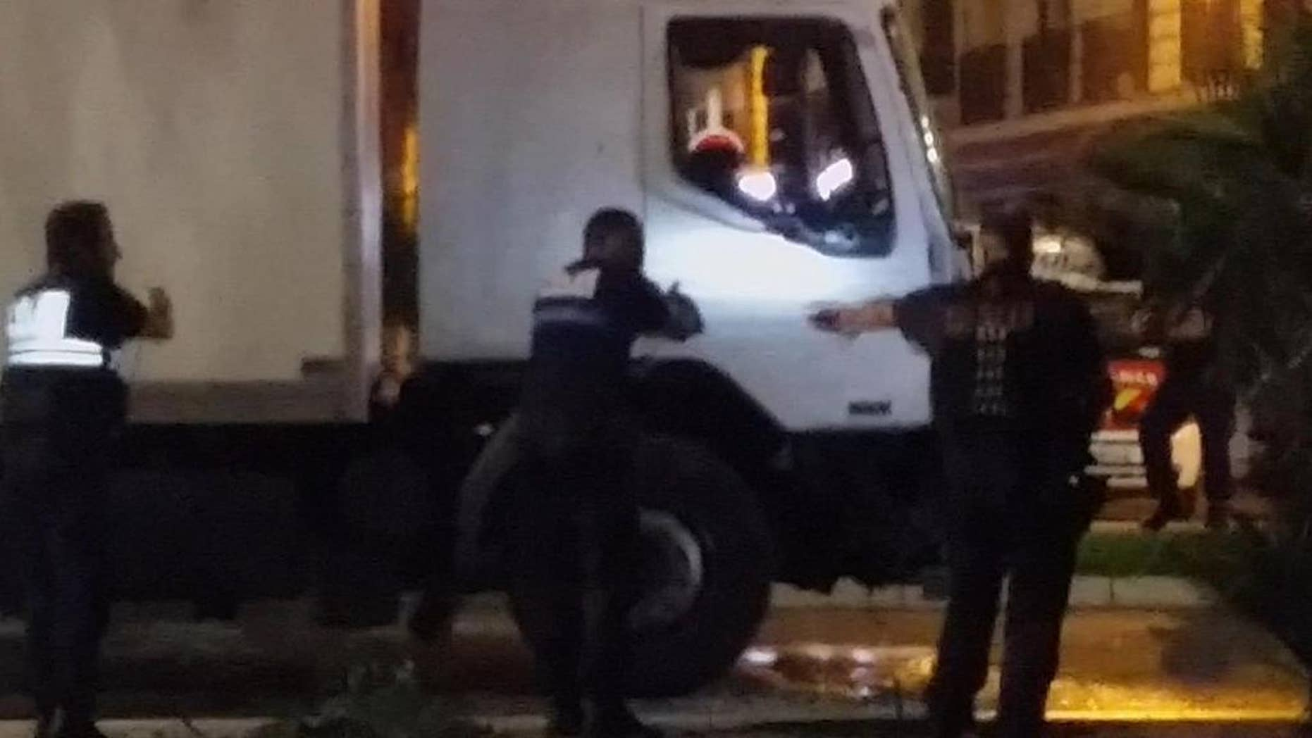FILE - Police approach the cab of a truck driven by Mohamed Lahouaiyej Bouhlel, a Tunisian who plowed through a crowded promenade, killing at least 84 people in Nice, France, in this July 14, 2016, file photo. Bouhlel's family and neighbors say he was indifferent to religion, but French authorities have linked the attack to Islamic State. (NADER EL SHAFEI via AP, File) MANDATORY CREDIT