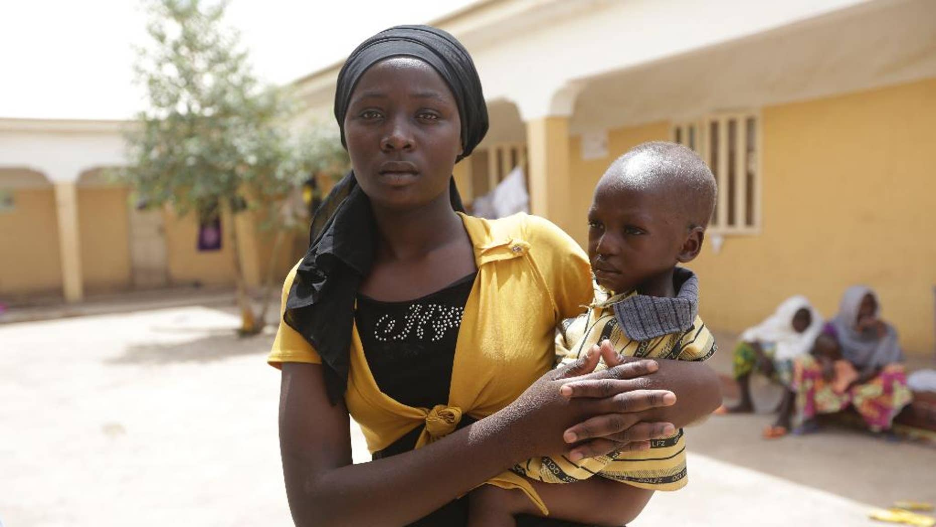 FILE - In this Monday, May 4, 2015 file photo, Binta Ibrahim holds an unidentified child after she described told how at 16 she rescued three children aged between 2 and 4, cared for them during a year of captivity under Boko Haram and brought them to the safety of the refugee camp in Yola. All 275 women, girls and children rescued from Boko Haram and taken to the safety of a northeast Nigerian refugee camp have been taken into military custody amid suspicions that some are aiding the Islamic extremists, a camp official and a Nigerian military intelligence officer said Wednesday May 20, 2015. (AP Photo/Sunday Alamba, File)