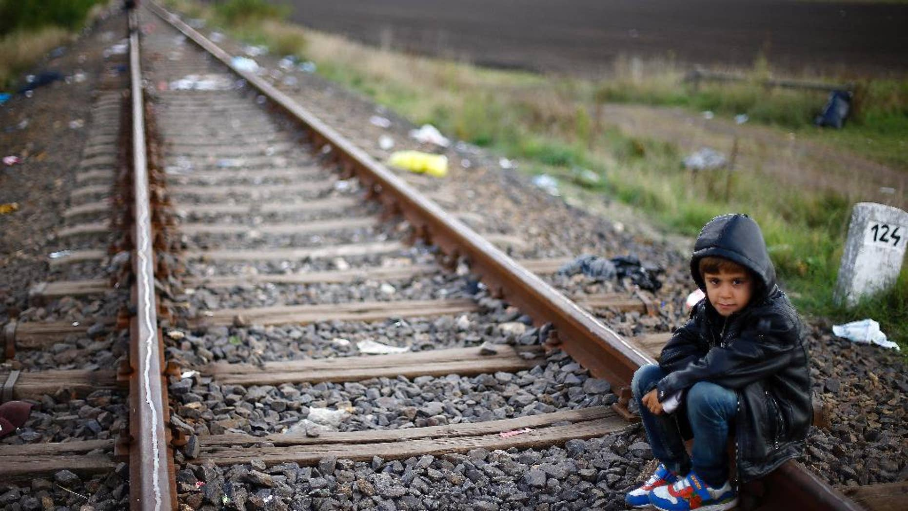 A young boy rests on the railway track near a temporary holding center for migrants near the border between Serbia and Hungary in Roszke, southern Hungary in Roszke, Saturday, Sept. 12, 2015. Leaders of the United Nations refugee agency warned Tuesday that Hungary faces a bigger wave of 42,000 asylum seekers in the next 10 days and will need international help to provide shelter on its border. (AP Photo/Matthias Schrader)