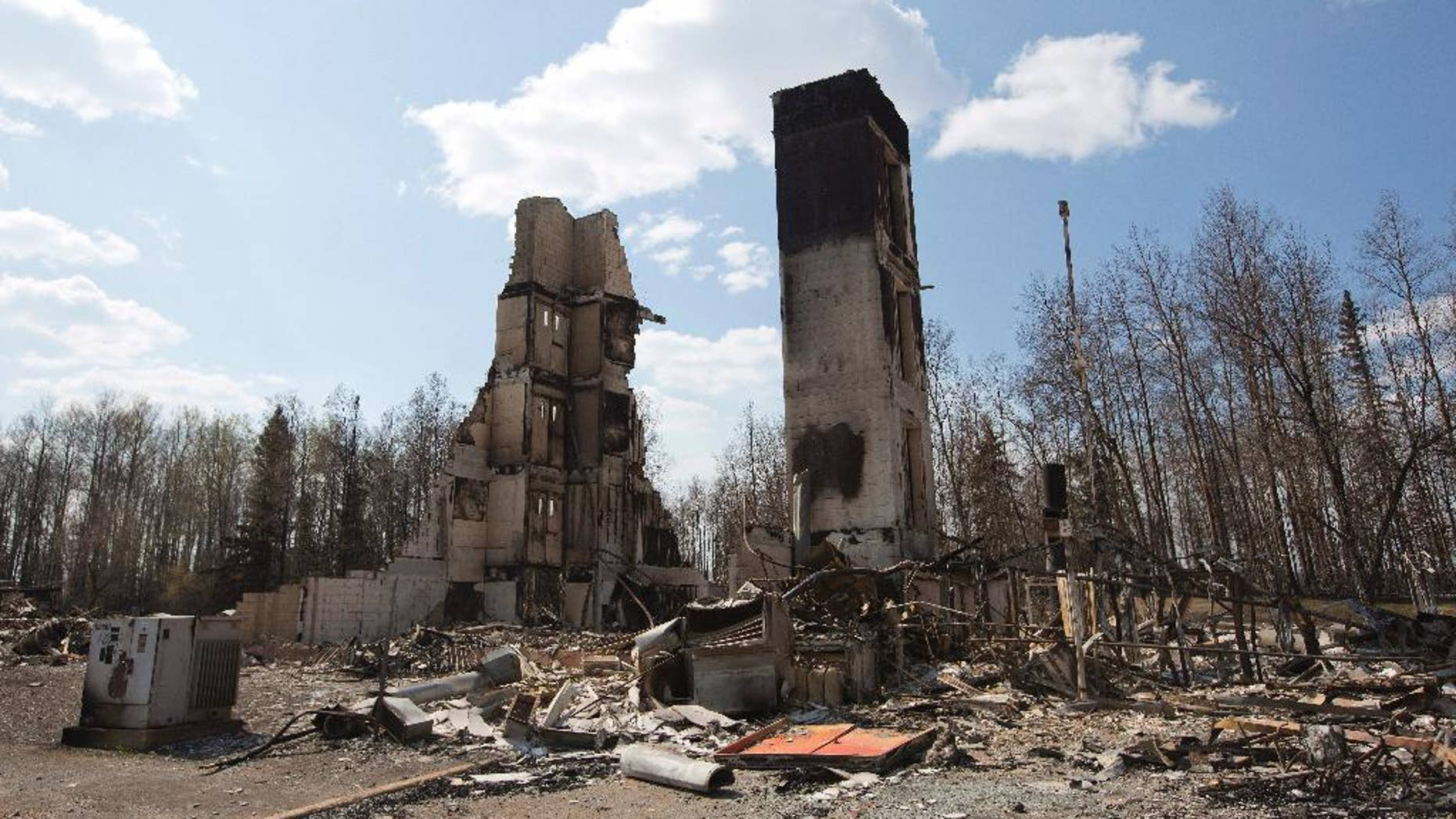A burned building stands among charred rubble in the neighborhood of Abasand in wildfire-ravaged Fort McMurray, Alberta, on Friday, May 13, 2016. (Jason Franson /The Canadian Press via AP) MANDATORY CREDIT