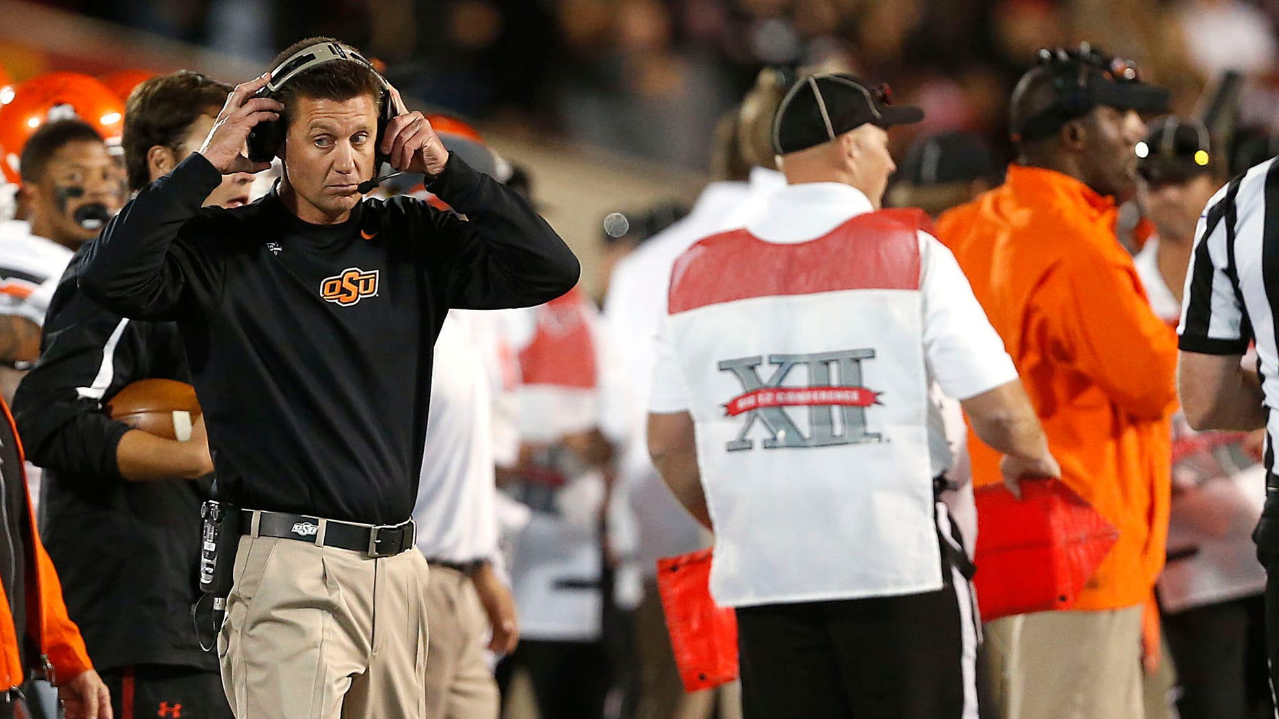 Oklahoma State coach Mike Gundy watches as his team competes against Texas Tech during their NCAA college football game in Lubbock, Texas, Saturday, Nov. 2, 2013. (AP Photo/Lubbock Avalanche-Journal,Stephen Spillman)