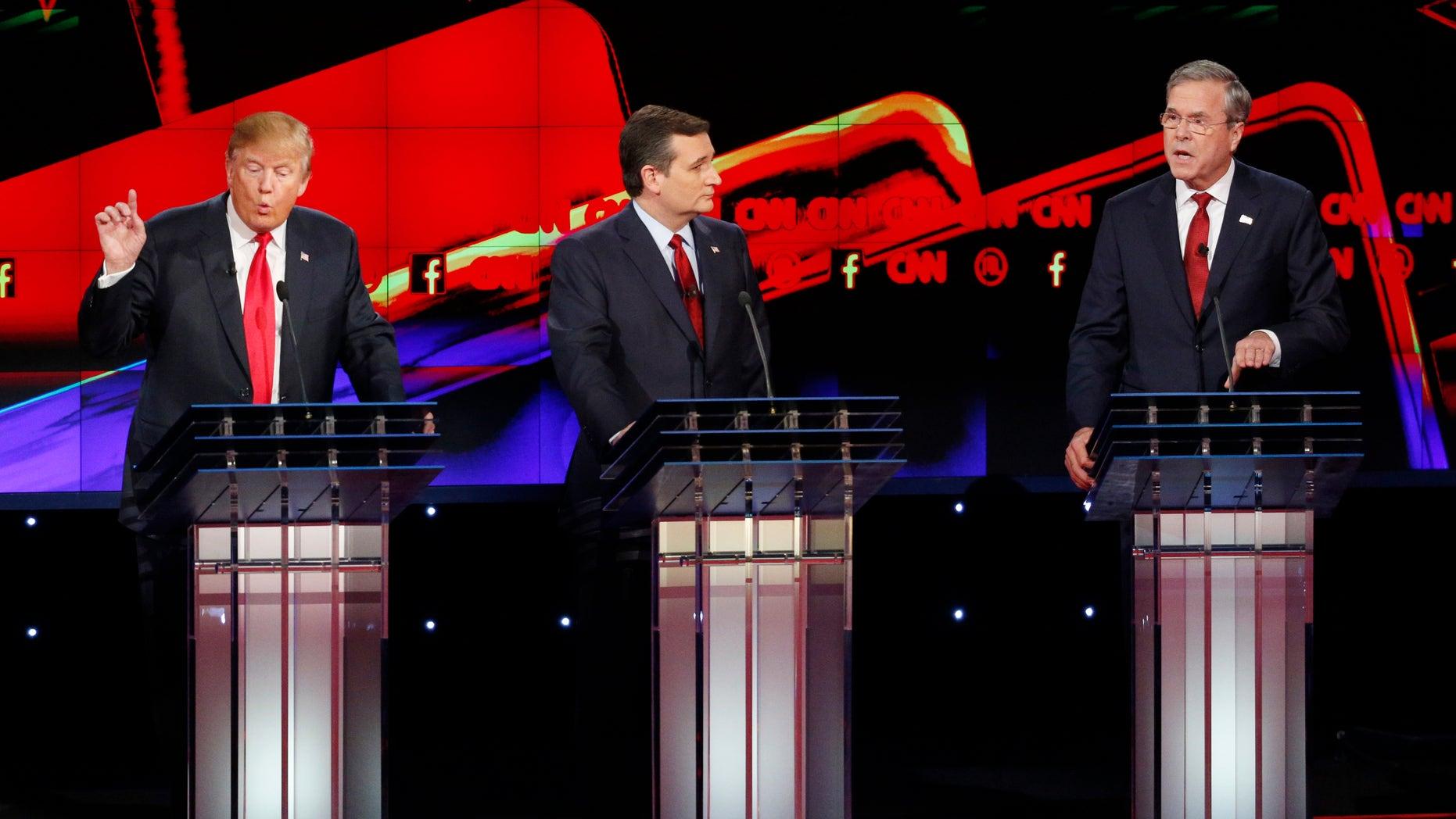 Donald Trump, a la izquierda, y Jeb Bush, a la derecha, hablan ante la mirada de Ted Cruz durante el debate republicano de CNN en el hotel y casino Venetian de Las Vegas, el martes 15 de diciembre de 2015 en Las Vegas. (AP Foto/John Locher)