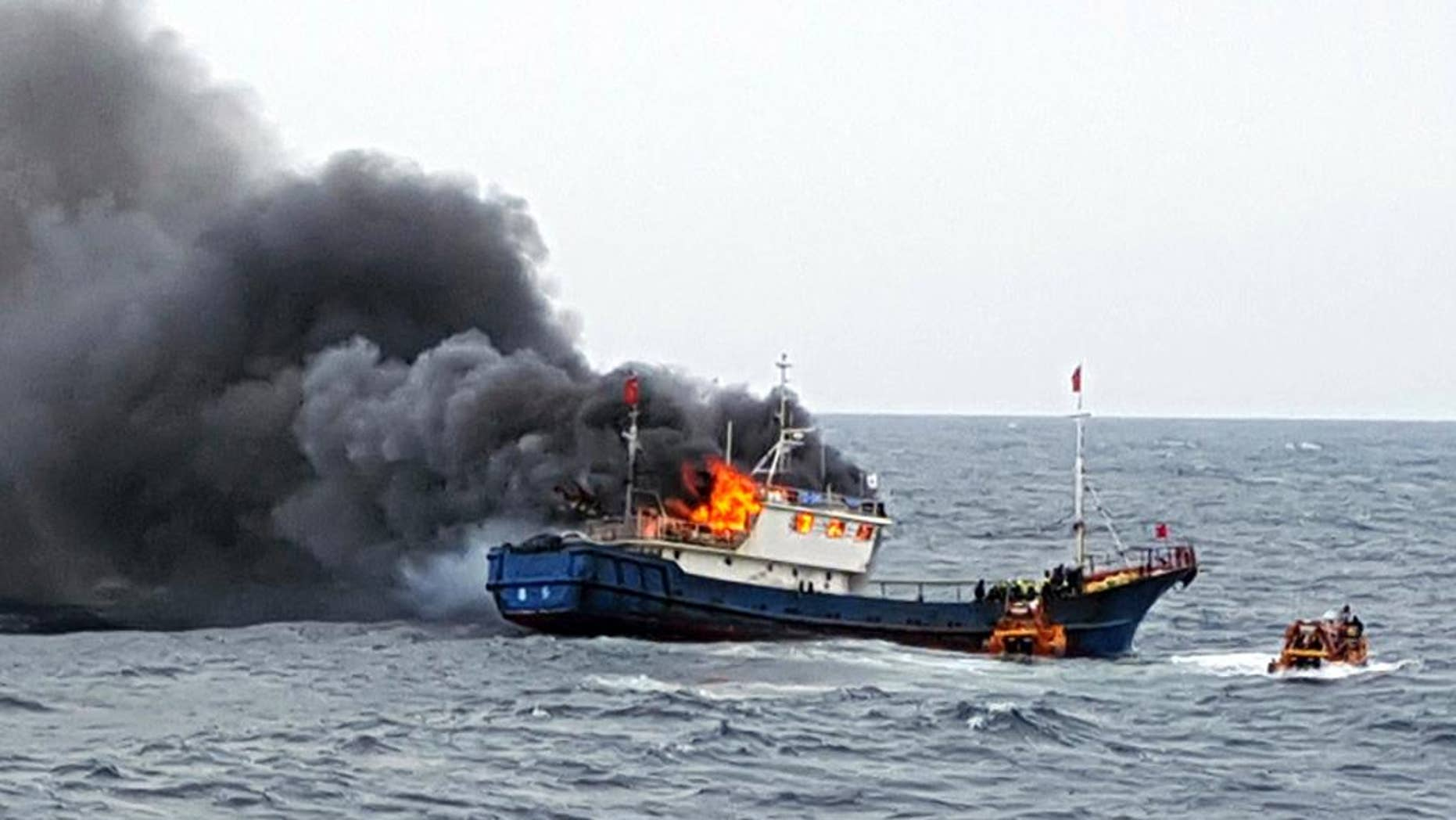 In this Thursday, Sept. 29, 2016 photo provided by the South Korean Mokpo Coast Guard, a Chinese fishing boat catches fires during an inspection by the South Korean coast guard in the water off Hong Island, South Korea. South Korea's coast guard said three Chinese fishermen have been found dead when a fire broke out on their boat after the coast guard fired a flashbang grenade at the vessel to stop it. (South Korean Mokpo Coast Guard via AP)
