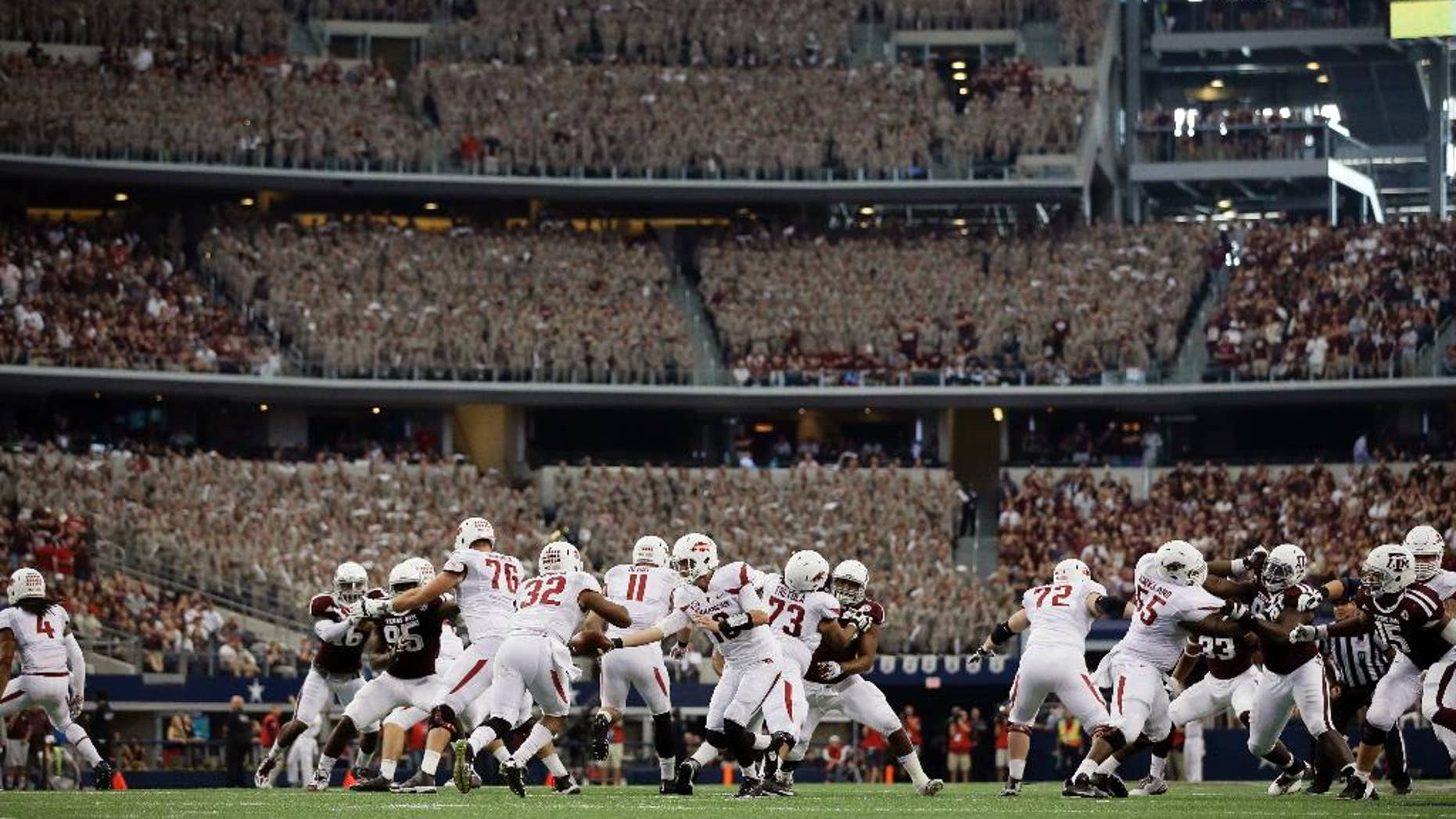 Arkansas quarterback Brandon Allen (10) hands off to running back Jonathan Williams (32) in the first half of an NCAA college football game against Texas A&M, Saturday, Sept. 27, 2014, in Arlington, Texas. The Aggie Corps. of Cadets fill the stadium seats at rear during the game. (AP Photo/Tony Gutierrez)