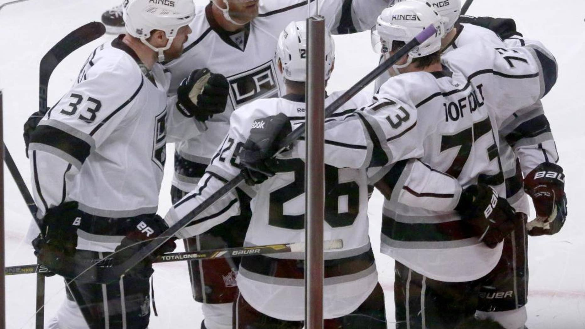 The Los Angeles Kings gather around center Tyler Toffoli as they celebrate Toffoli's goal during the third period of Game 2 of the Western Conference finals in the NHL hockey Stanley Cup playoffs against the Chicago Blackhawks on Wednesday, May 21, 2014, in Chicago. From left are Willie Mitchell (33), Jeff Carter (77), Slava Voynov (26), Toffoli, and Tanner Pearson. (AP Photo/Charles Rex Arbogast)