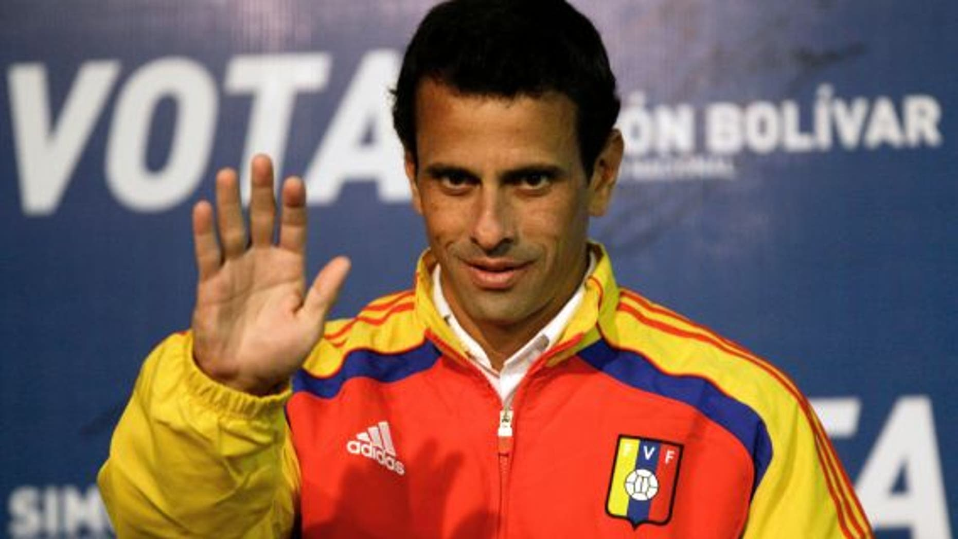 April 13, 2013: Opposition presidential candidate Henrique Capriles waves as he arrives to a news conference in Caracas, Venezuela.