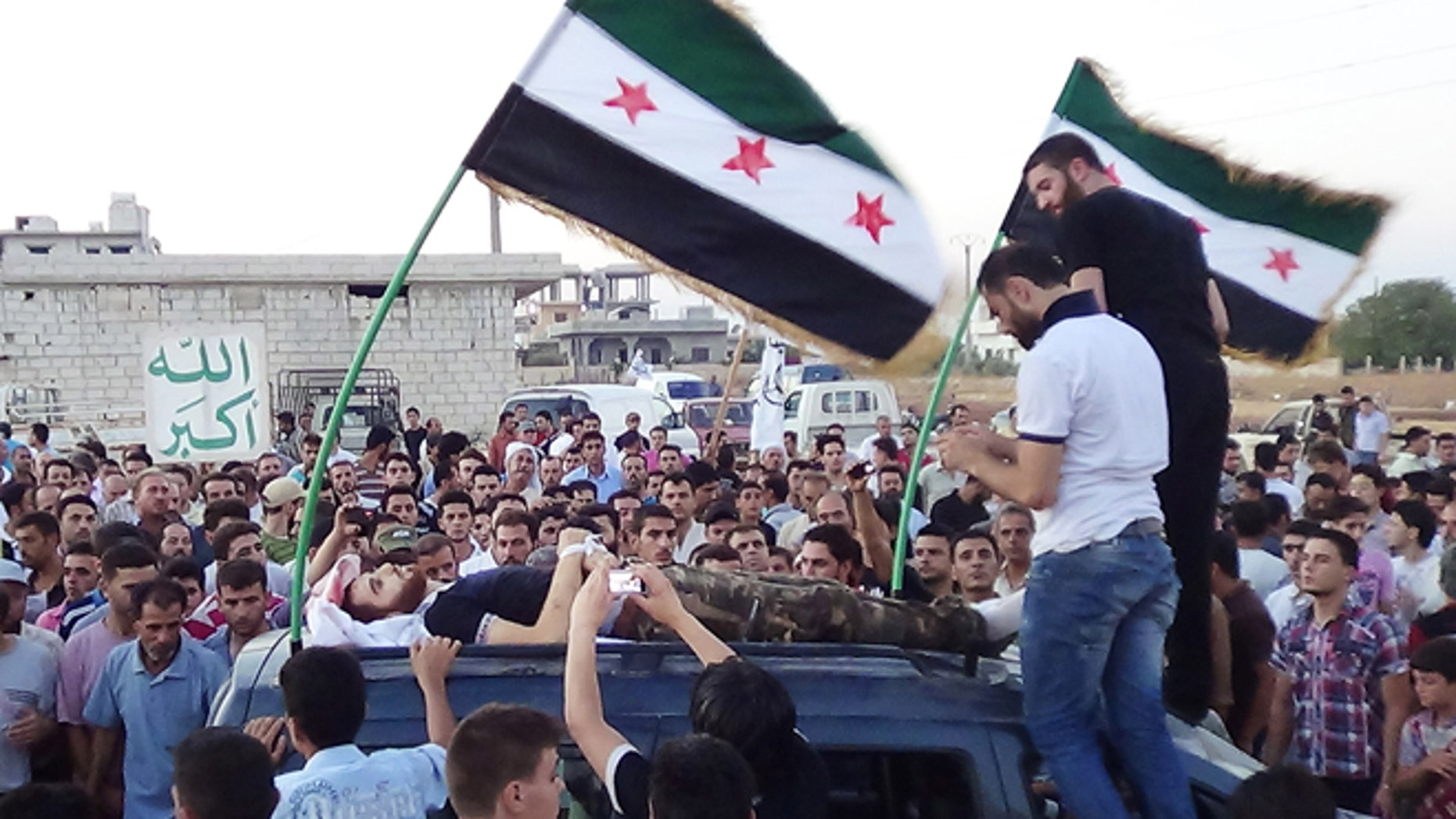 """In this citizen journalism image provided by Shaam News Network SNN, taken on Tuesday, Aug. 7, 2012, Syrians attend the funeral procession of a man killed in Idlib province, Syria. Arabic, left, reads, """"God is great."""""""