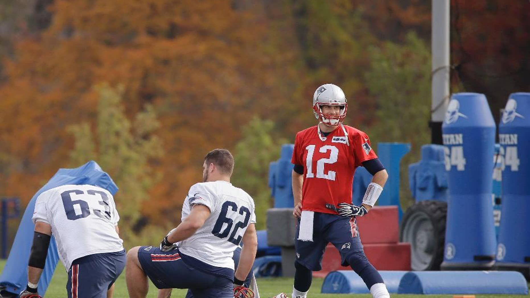 New England Patriots quarterback Tom Brady (12) stretches with offensive linemen Ryan Wendell (62) and Dan Connolly (63) before practice begins at the NFL football team's facility Wednesday, Oct. 29, 2014 in Foxborough, Mass. The Patriots (6-2) will play the Denver Broncos (6-1) Sunday in Foxborough. (AP Photo/Stephan Savoia)