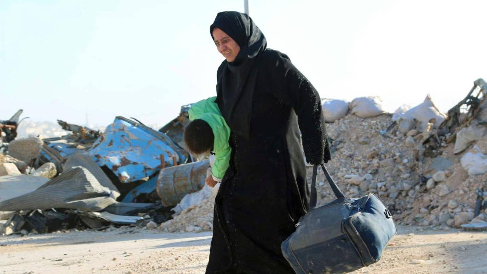 This Sunday, Nov. 27, 2016 photo provided by the Rumaf, a Syrian Kurdish activist group, which has been authenticated based on its contents and other AP reporting, shows A Syrian woman carrying her child in one hand and a bag in the other, as she flees rebel-held eastern neighborhoods of Aleppo into the Sheikh Maqsoud area that is controlled by Kurdish fighters, Syria. Syrian state media is reporting that government forces have captured the eastern Aleppo neighborhood of Sakhour, putting much of the northern part of Aleppo's besieged rebel-held areas under state control. (The Rumaf via AP)