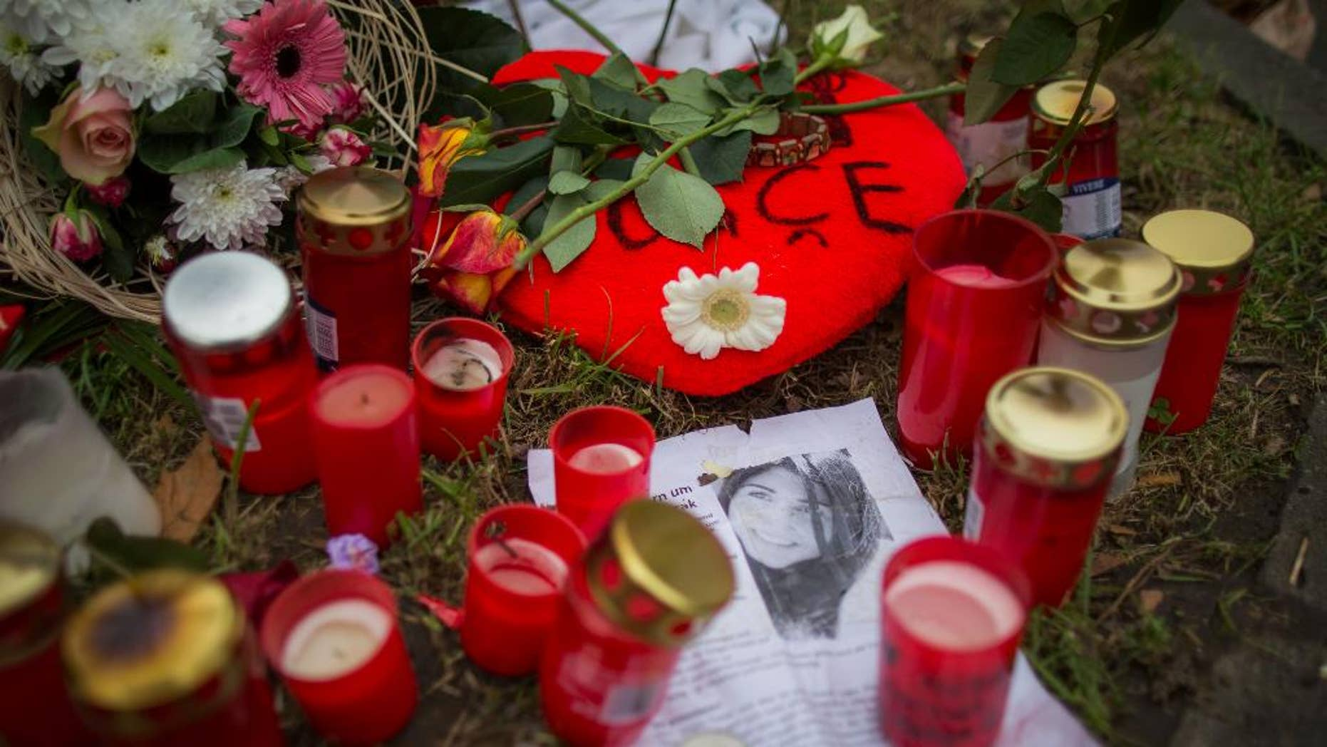 Candles and flowers are placed on the parking lot where Tugce was fatally injured two weeks ago in Offenbach, Germany, Monday Dec.1, 2014. Germany's president is considering awarding a posthumous medal to the  young woman killed after defending two teenage girls from male harassment.   German news agency dpa reported Sunday that President Joachim Gauck was mulling the honor amid an outpouring of public outrage over the killing.   Student teacher Tugce Albayrak died Friday, her 23rd birthday, after her family gave doctors permission to switch off her life support.  (AP Photo/dpa,Frank Rumpenhorst)