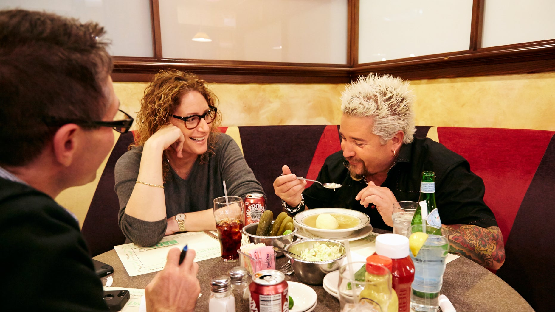 Dec. 9, 2013: Food Network star Guy Fieri, right, tasting matzo ball soup  at Ben's Deli as comedian Judy Gold, center, and AP Food Editor J.M Hirsch look on.