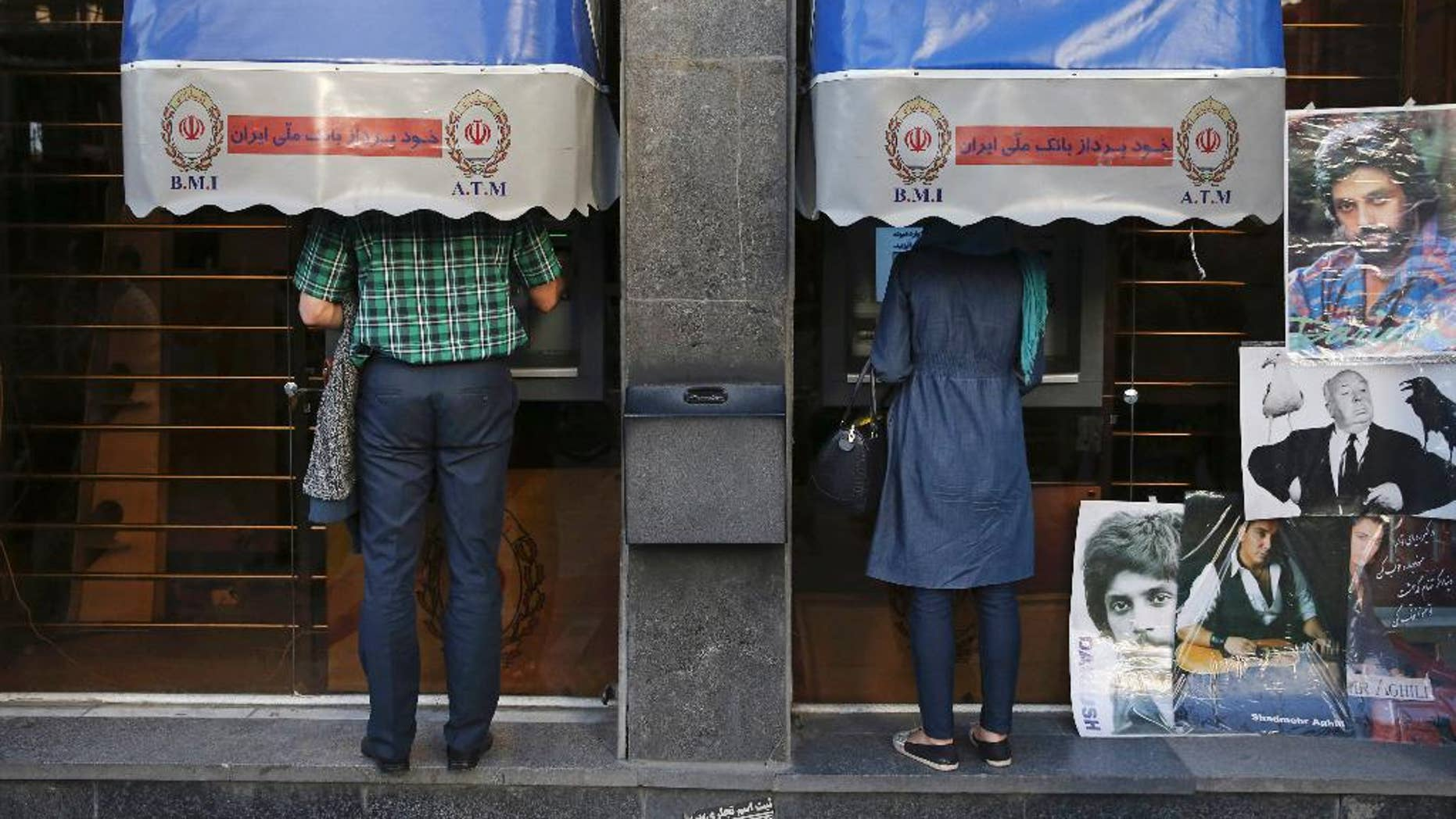 FILE -- In this April 4, 2015 file photo, Iranians use ATM machines of Bank Melli Iran in downtown Tehran, Iran. Iranian media are saying the country's banks will begin issuing credit cards for the first time in decades. Reports by several newspapers, including the daily Donya-e-Eqtesad, Monday, Sept. 26, 2016 said the cards will be for domestic use only and do not involve any sort of partnership with a major international credit card company. So far, Iranian banks have only issued debit and prepaid cards. (AP Photo/Vahid Salemi, File)